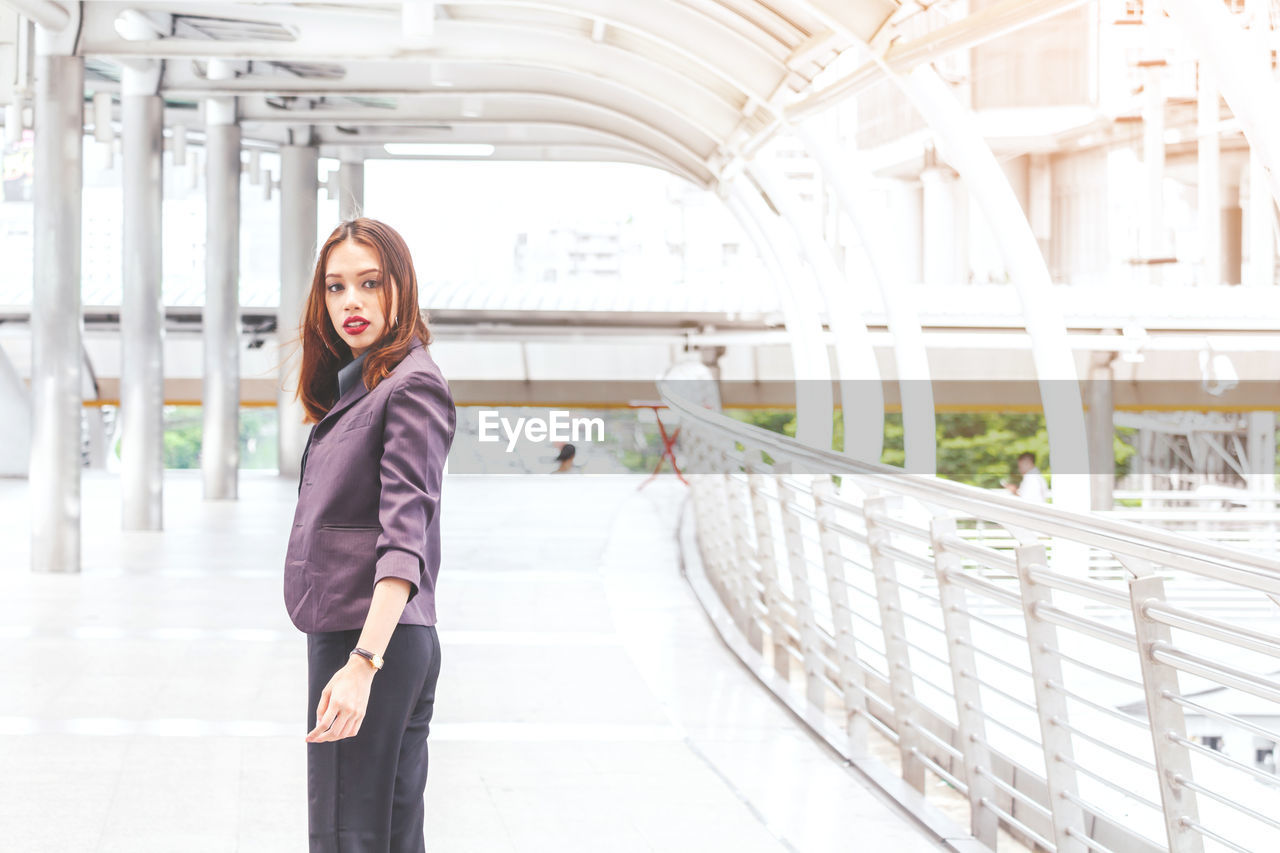 Portrait Of Young Businesswoman Standing On Elevated Walkway