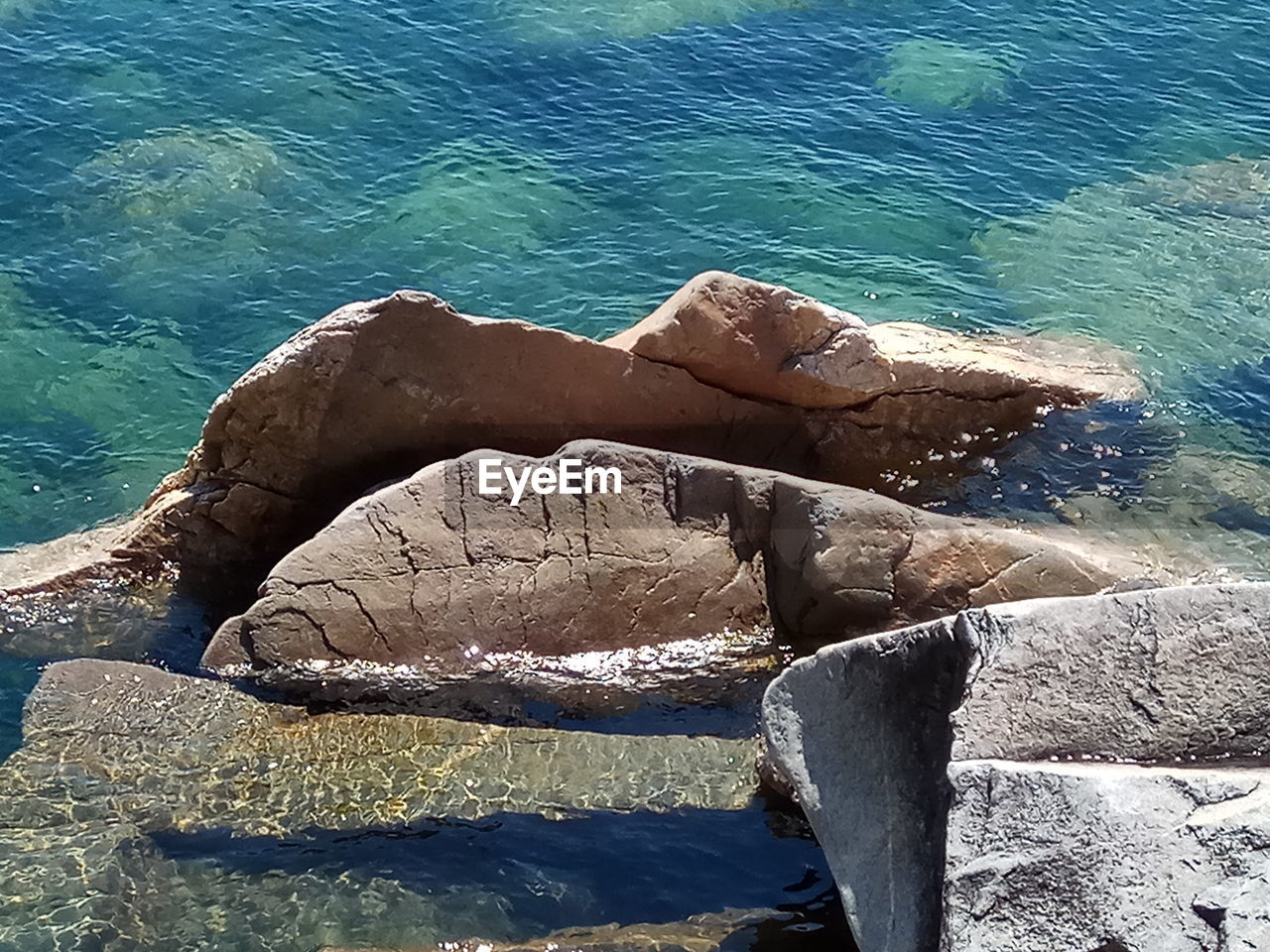 water, sea, rock, solid, rock - object, nature, day, beauty in nature, sunlight, beach, no people, high angle view, tranquility, rock formation, land, outdoors, tranquil scene, motion, blue