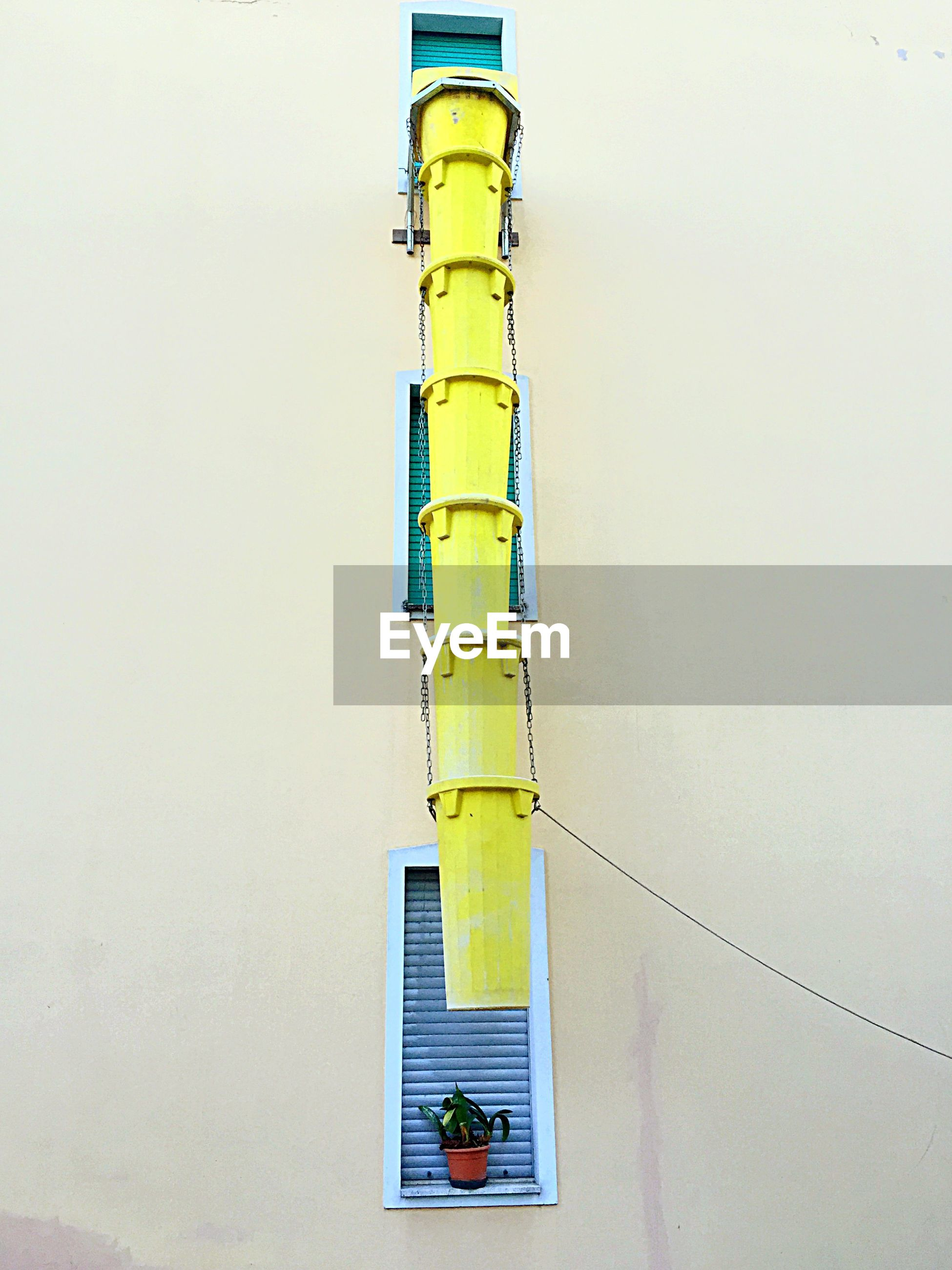 Low angle view of yellow pipe against building