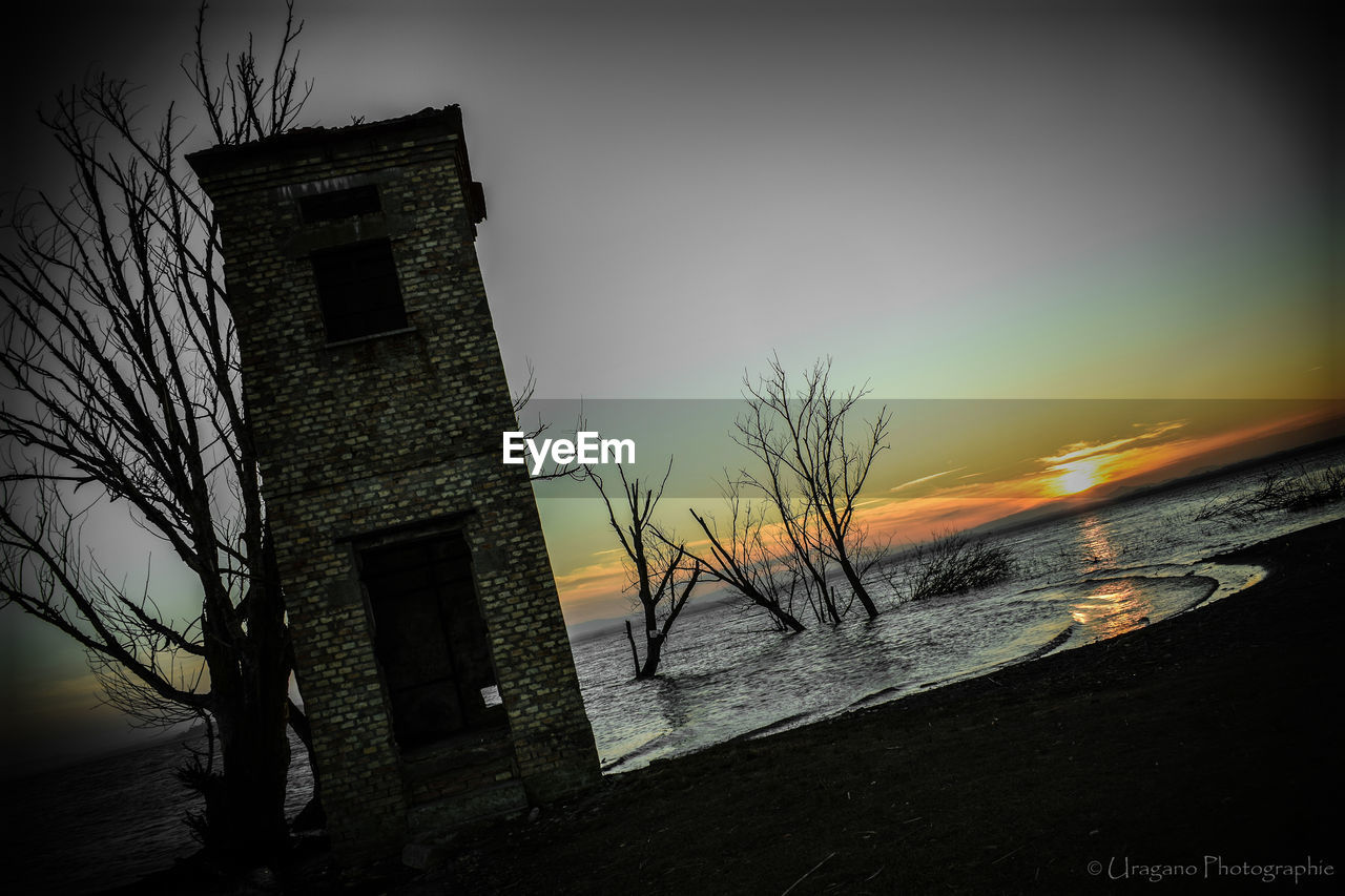 architecture, sky, sunset, sea, building exterior, water, built structure, no people, outdoors, nature, low angle view, bare tree, beauty in nature, beach, scenics, horizon over water, tree, day
