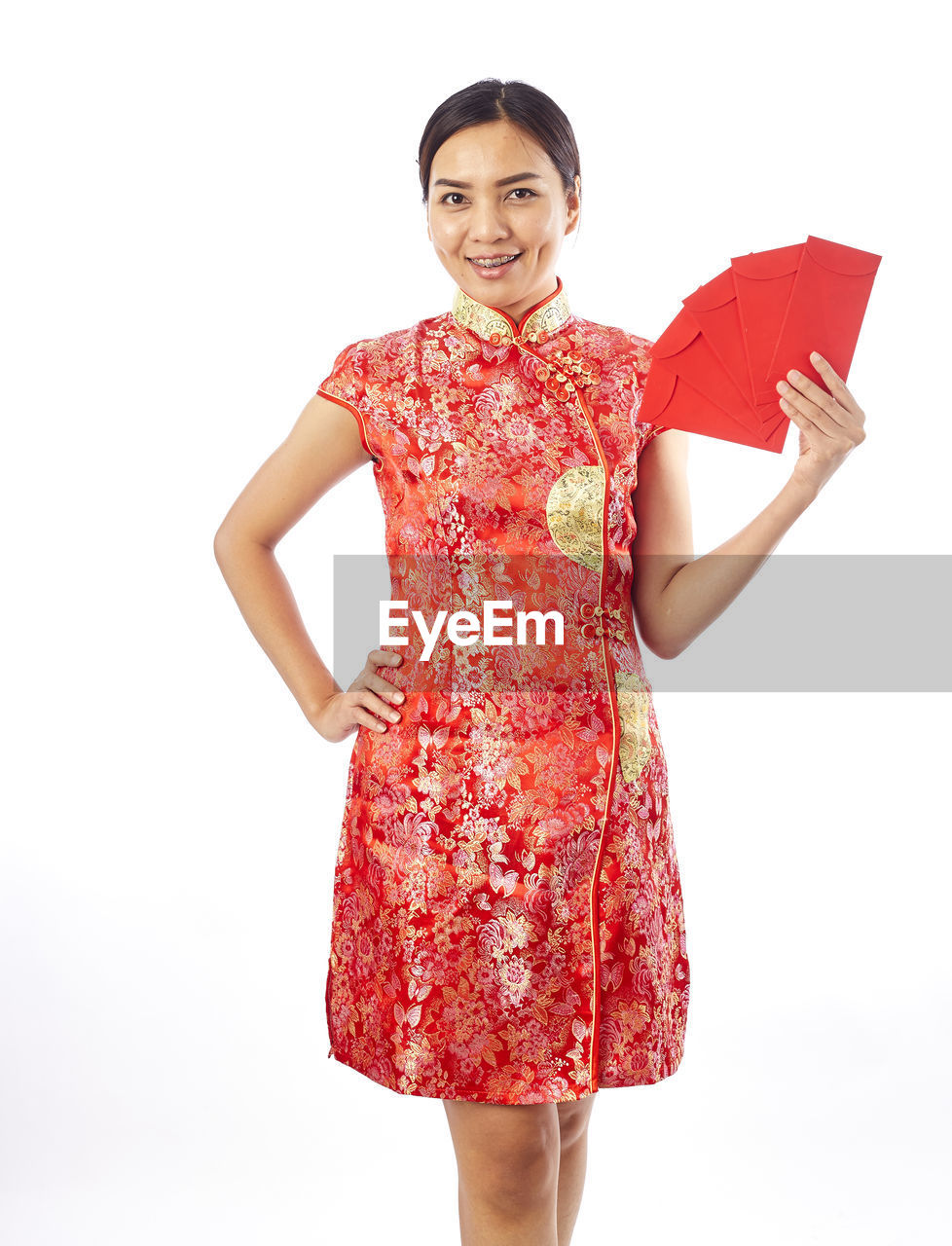 Woman wearing red traditional clothing while standing against white background