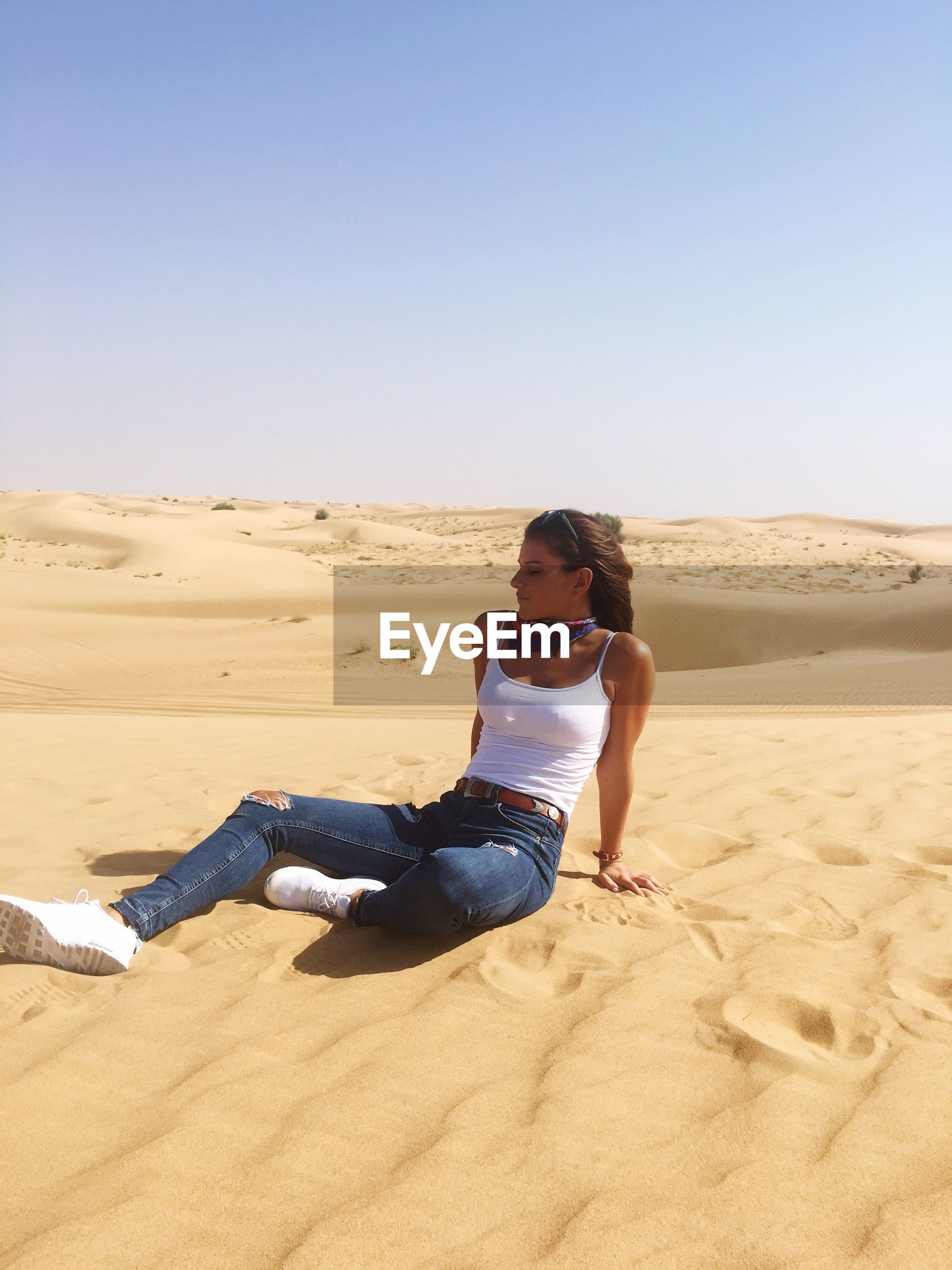 Young woman sitting on sand at desert against clear sky during sunny day