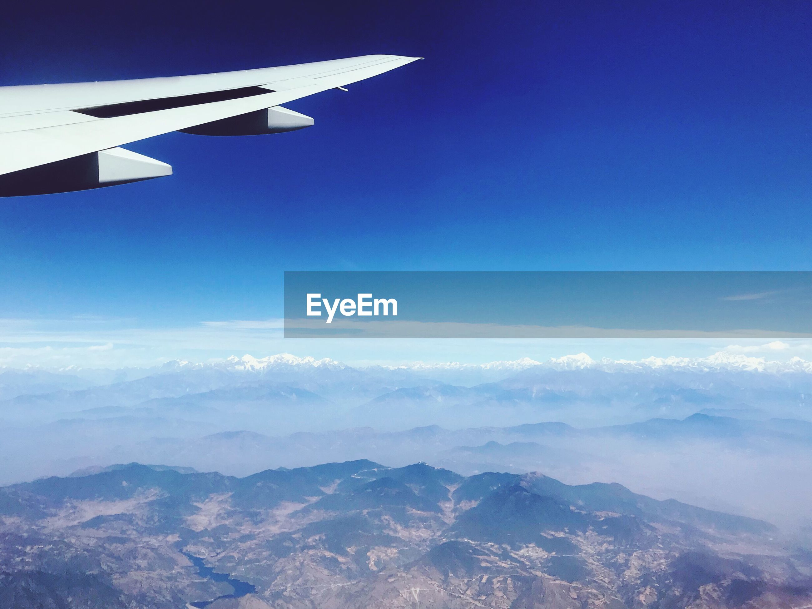AIRPLANE FLYING OVER MOUNTAINS AGAINST BLUE SKY