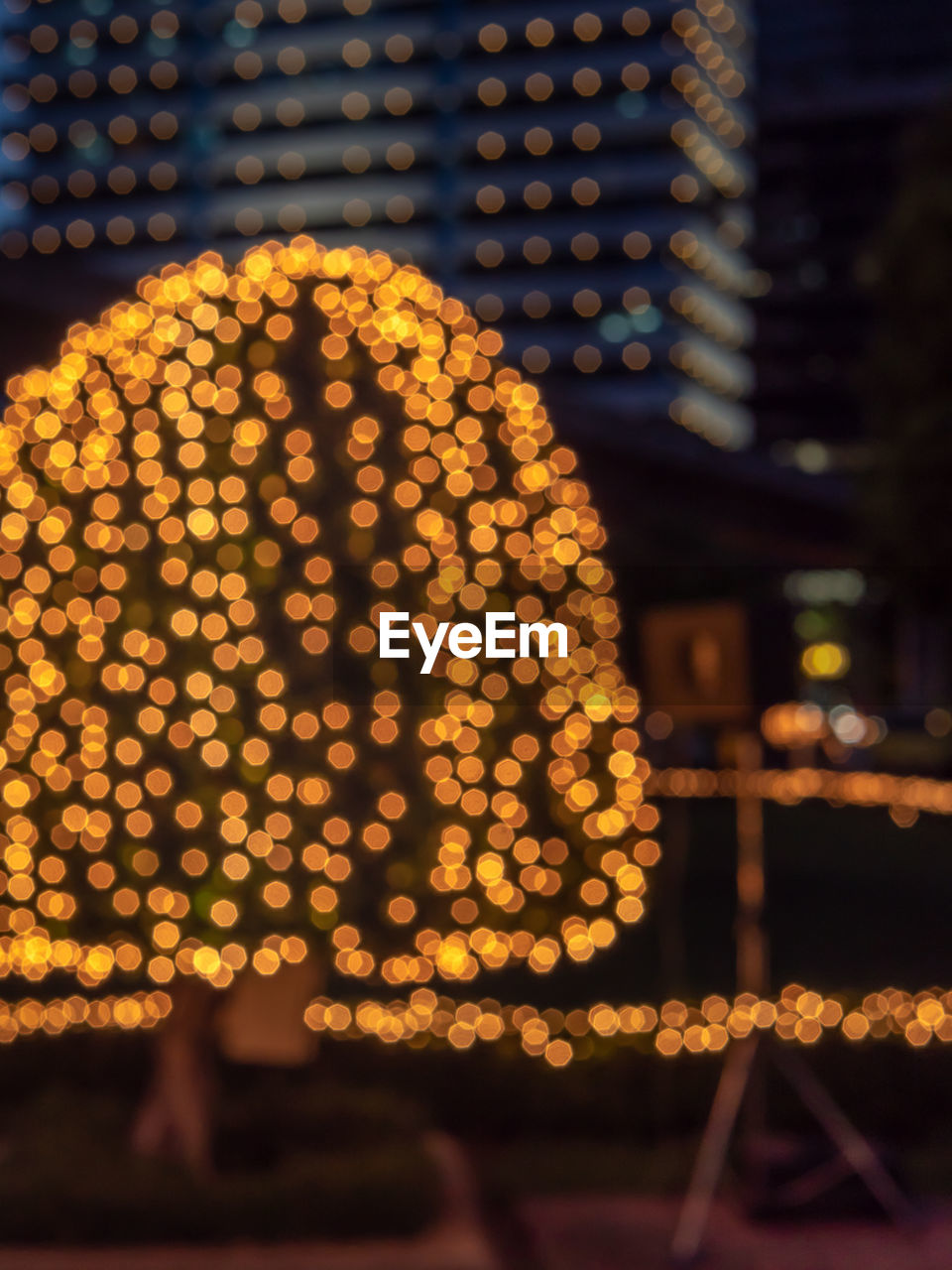 illuminated, night, architecture, focus on foreground, glowing, real people, christmas lights, lighting equipment, decoration, built structure, defocused, building exterior, shape, city, celebration, lifestyles, christmas, christmas decoration, pattern, outdoors, light