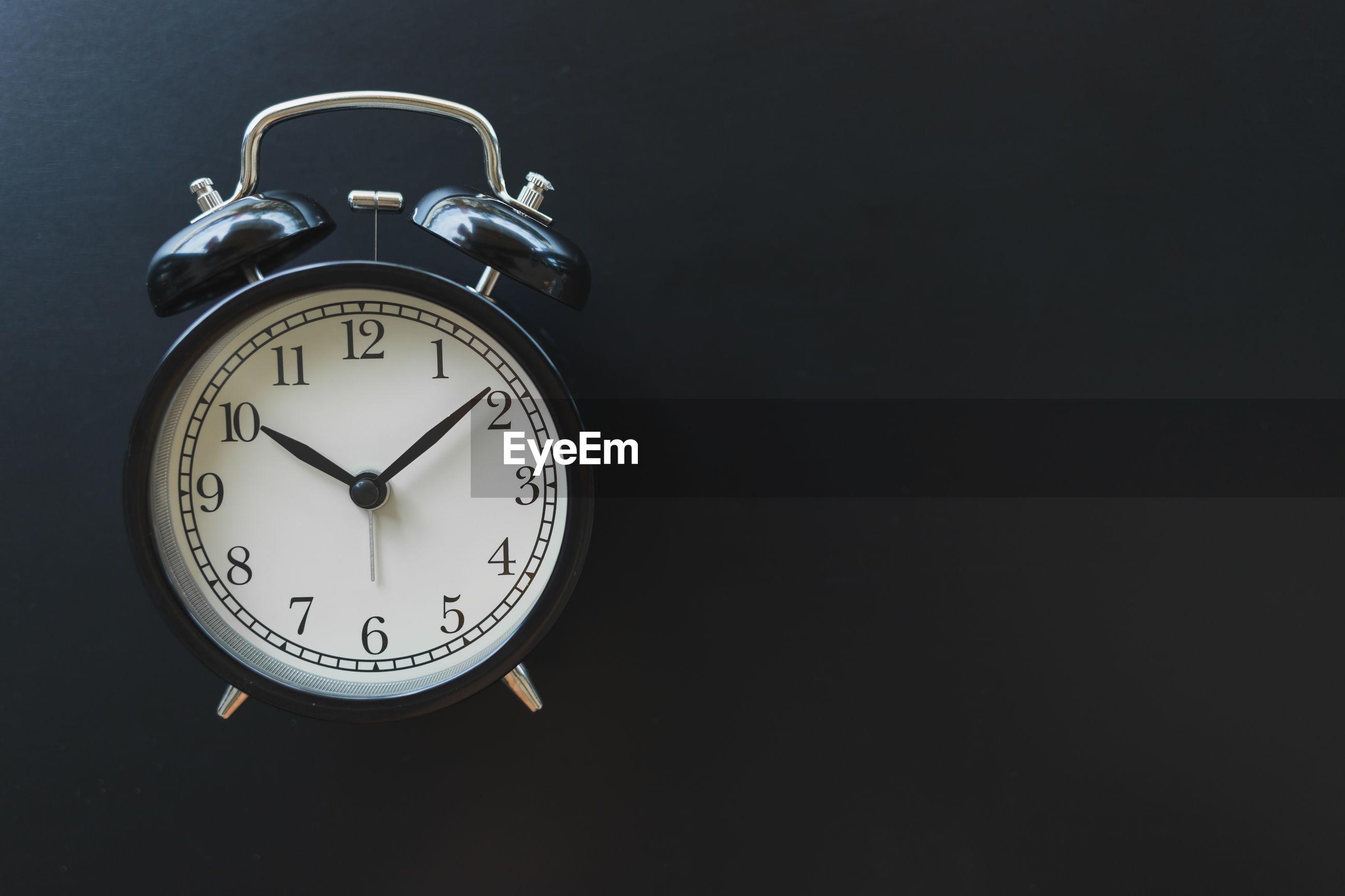 Close-up of alarm clock against black background