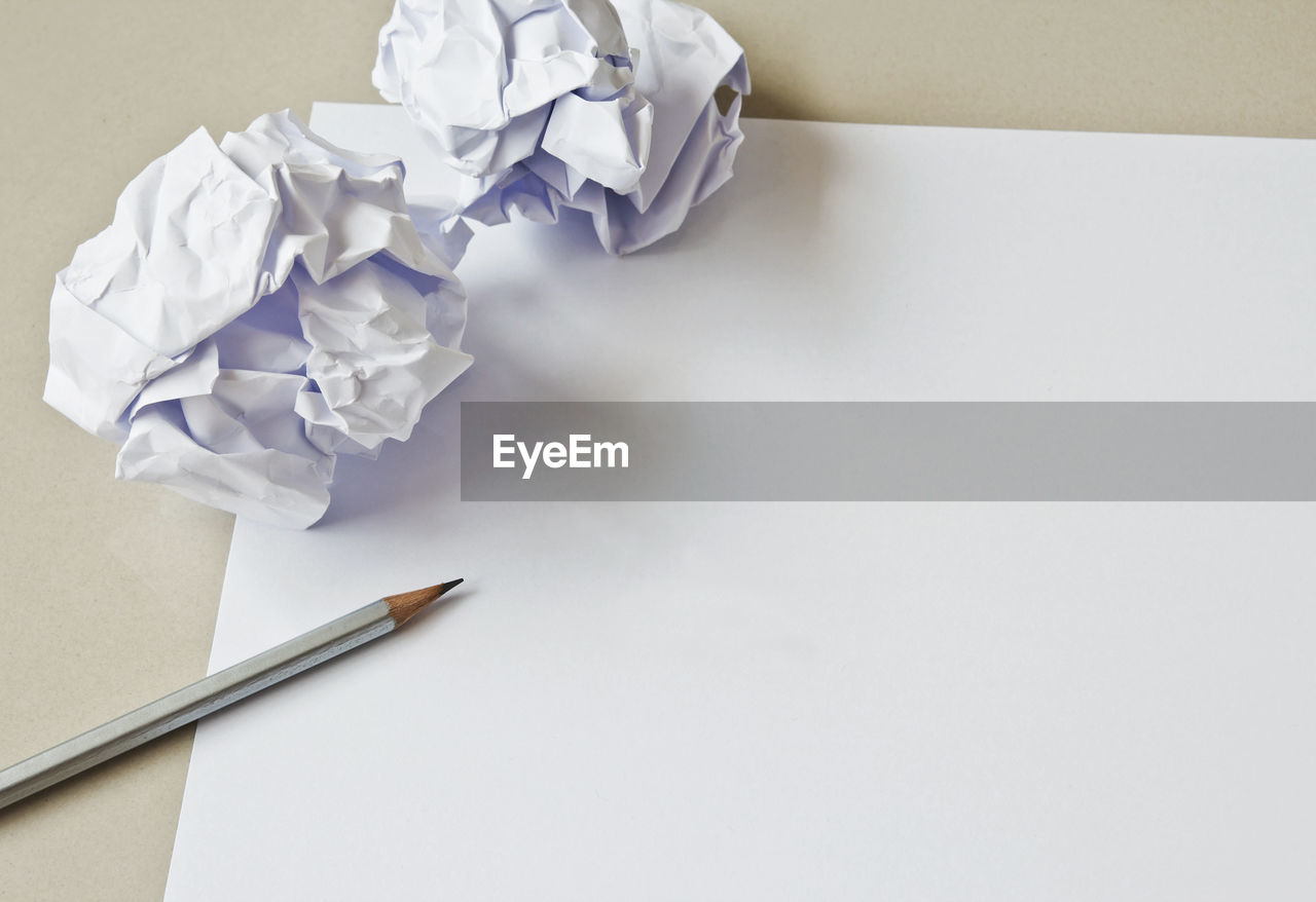 HIGH ANGLE VIEW OF WHITE AND PAPER ON TABLE