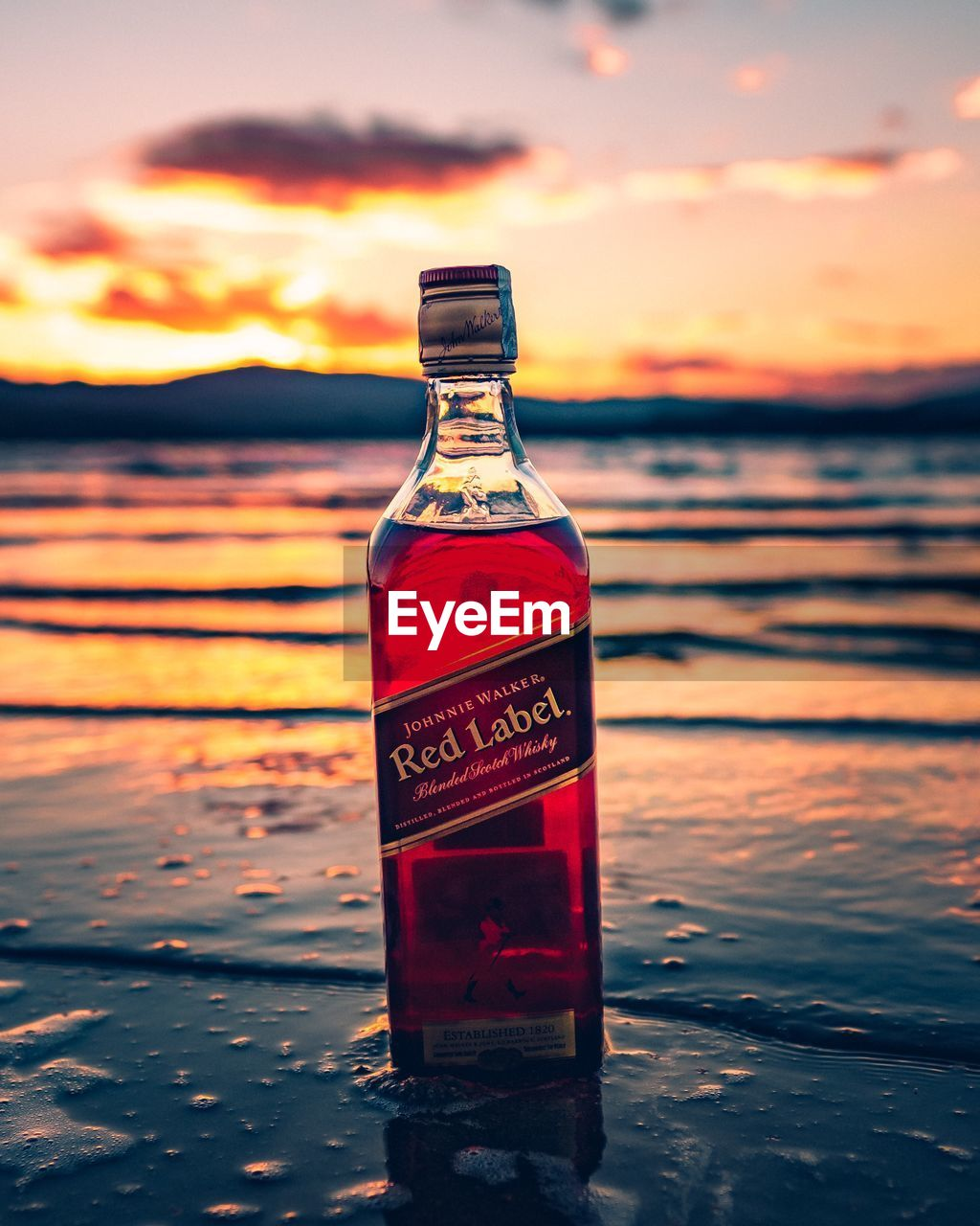 bottle, sunset, water, container, sky, orange color, focus on foreground, nature, sea, food and drink, glass - material, no people, close-up, drink, refreshment, transparent, cloud - sky, alcohol, beach