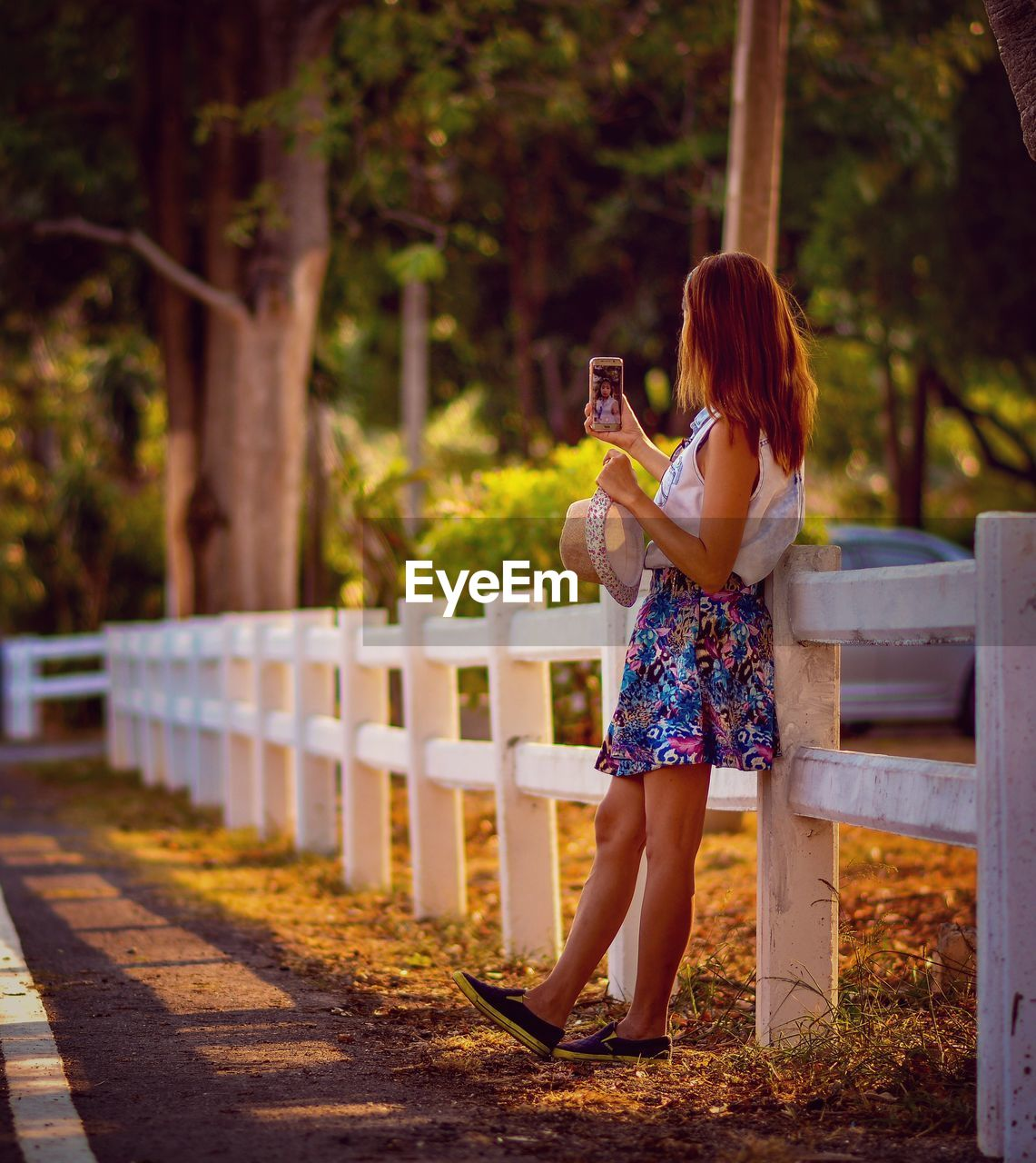 Woman taking selfie while standing on footpath