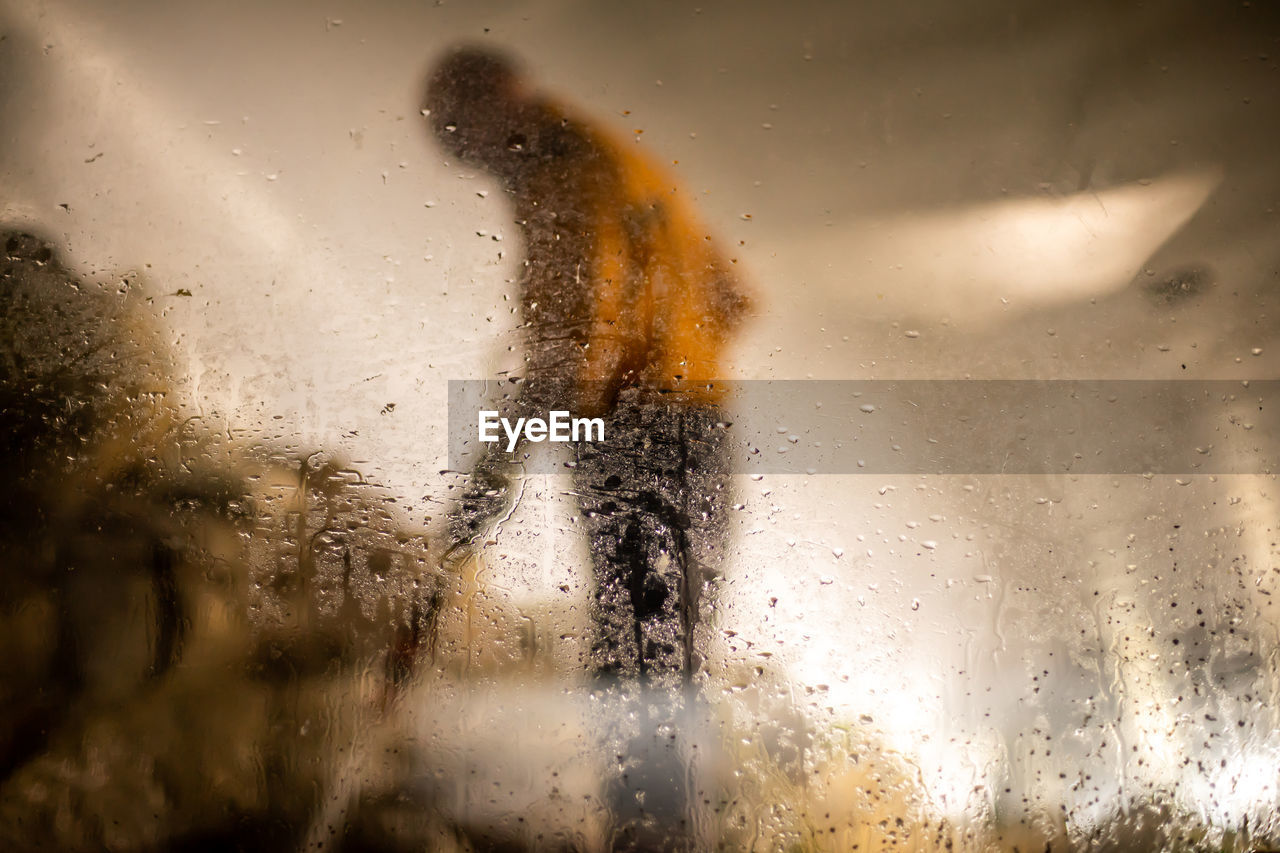 Side View Of Man Seen Through Wet Car Window During Rainy Season