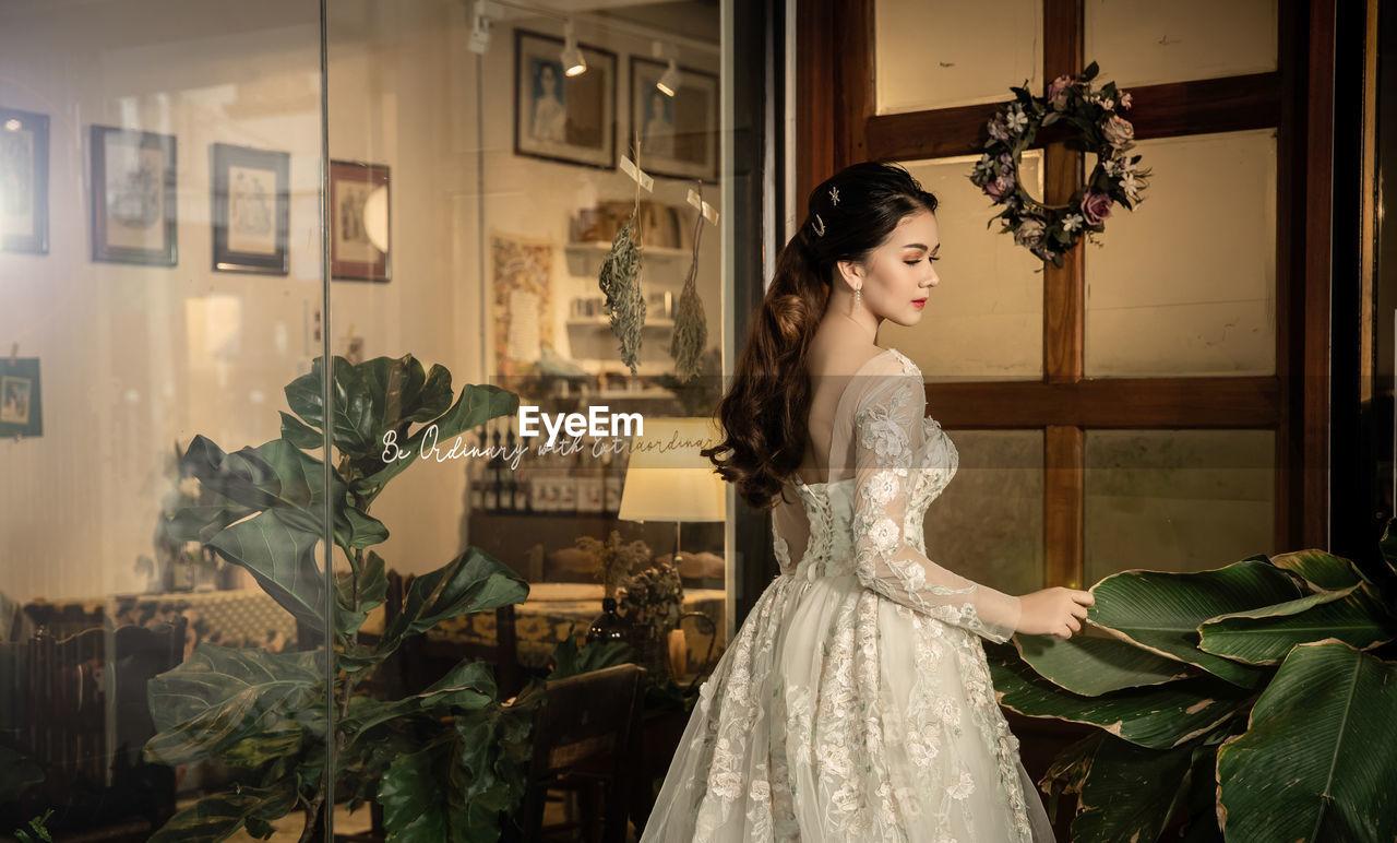 Woman wearing wedding dress while standing glass door
