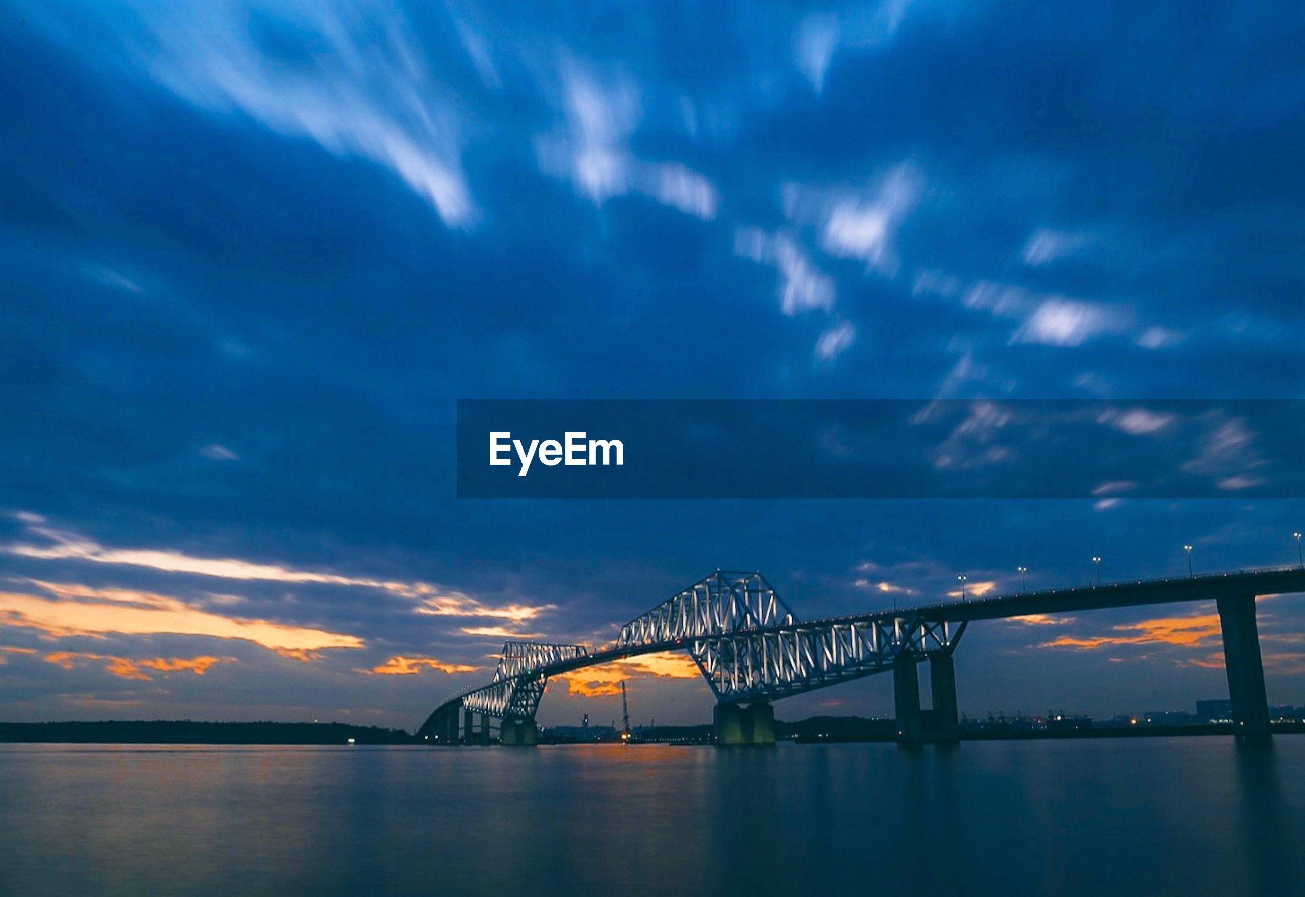Illuminated bridge over sea against sky at sunset