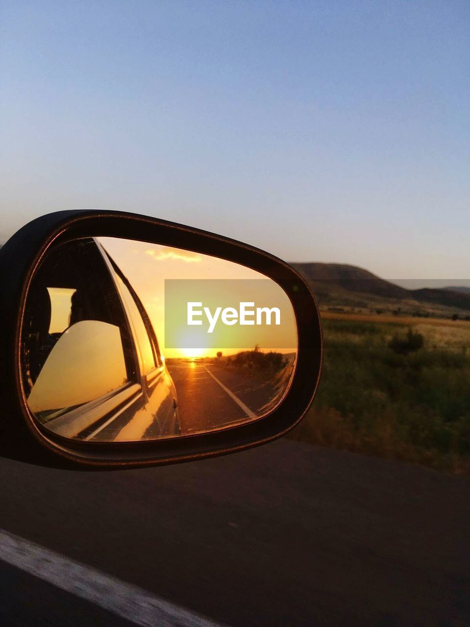 side-view mirror, car, transportation, reflection, sunset, road, land vehicle, vehicle mirror, mode of transport, nature, clear sky, no people, outdoors, sky, landscape, close-up, day