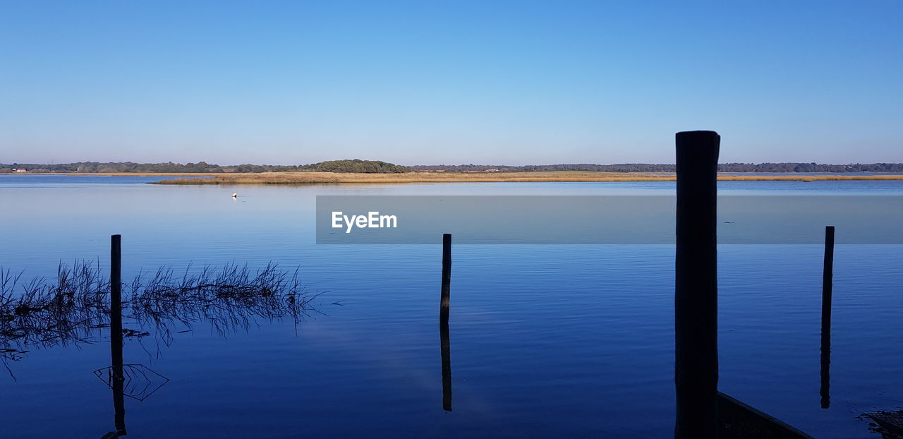 water, tranquility, tranquil scene, sky, scenics - nature, beauty in nature, lake, post, blue, no people, wooden post, wood - material, copy space, clear sky, nature, non-urban scene, idyllic, waterfront, reflection, outdoors
