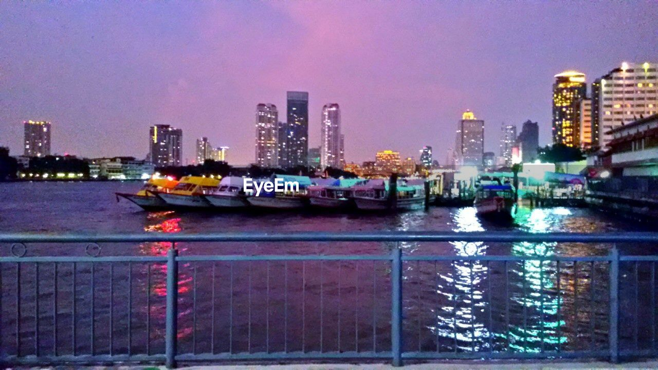 building exterior, architecture, city, built structure, waterfront, illuminated, skyscraper, water, transportation, night, nautical vessel, outdoors, city life, cityscape, urban skyline, no people, modern, sea, sky, clear sky