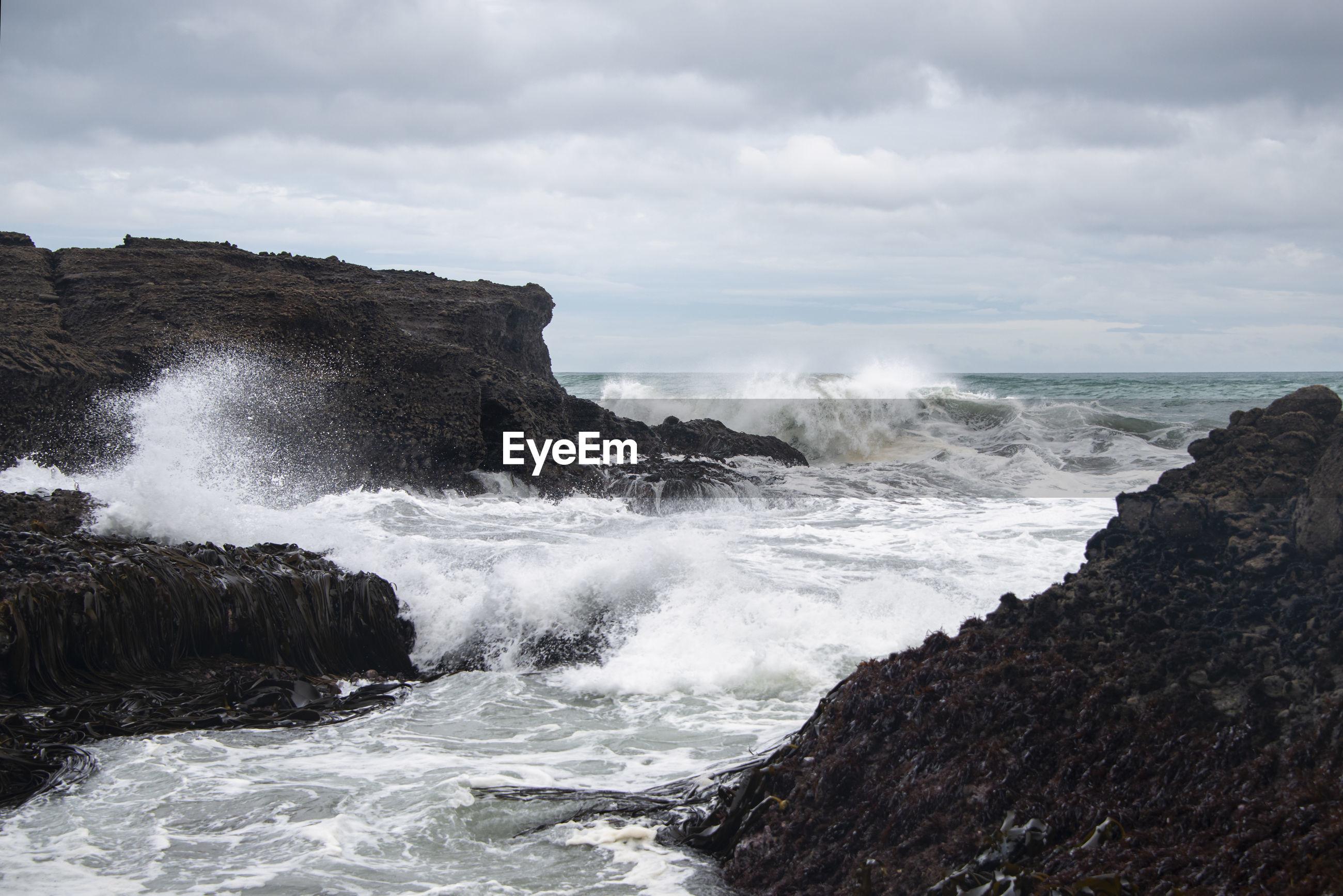 WAVES SPLASHING ON ROCKS AT SEA AGAINST SKY