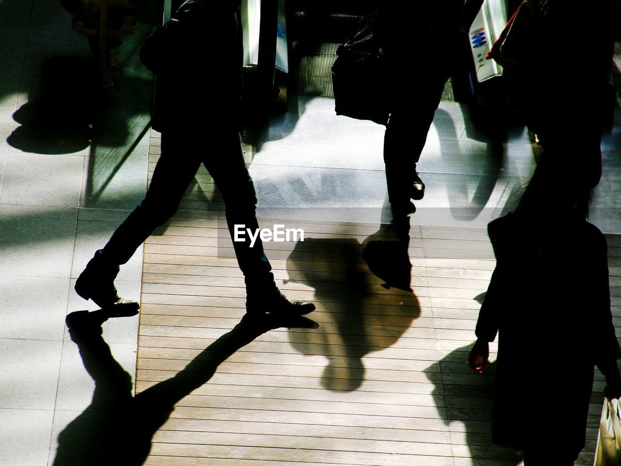 indoors, low section, real people, human leg, group of people, medium group of people, hardwood floor, men, shadow, women, day, standing, lifestyles, full length, people