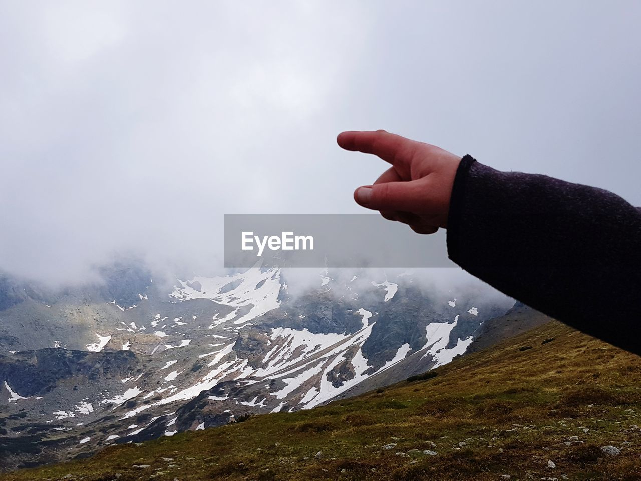 Cropped hand pointing against snowcapped mountains