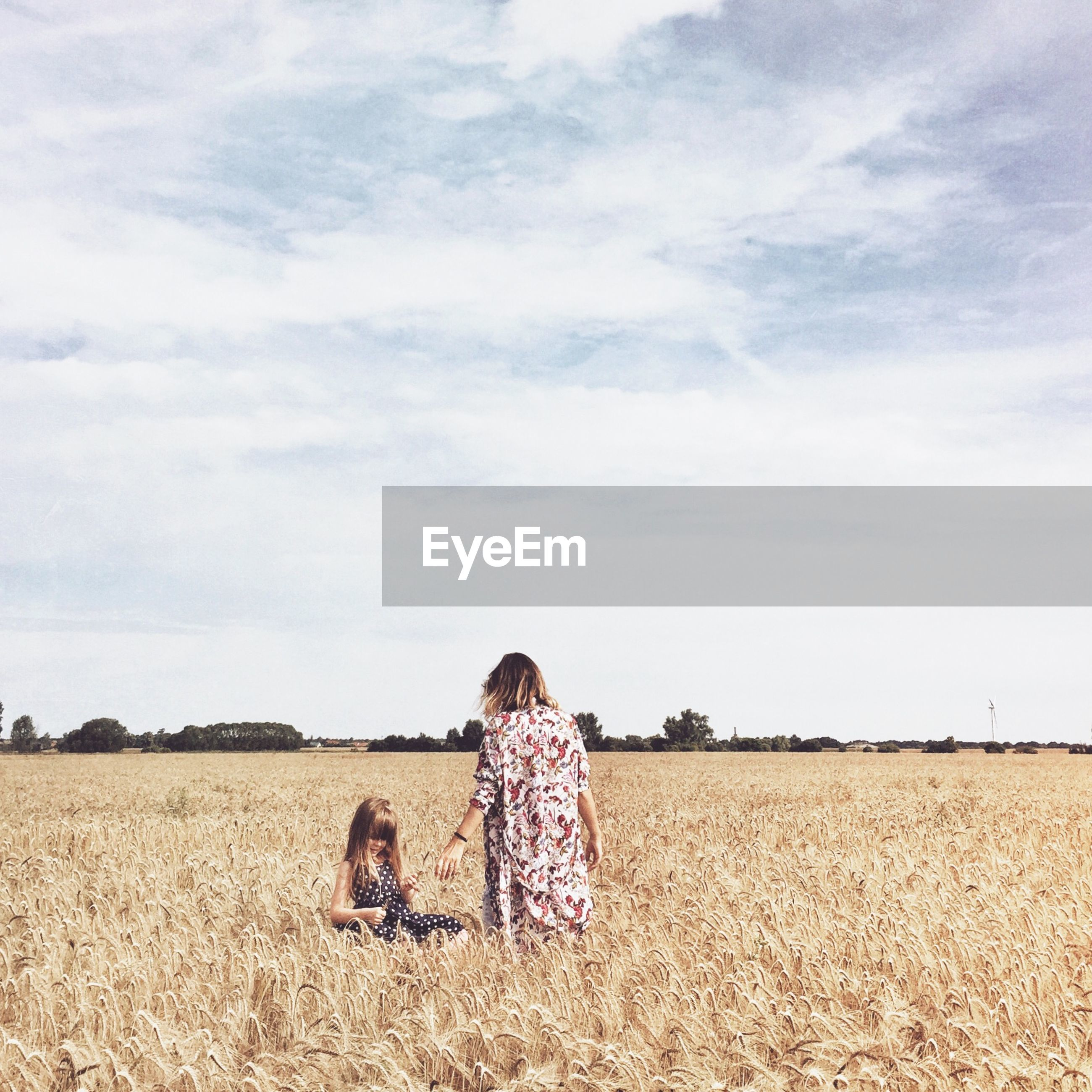 Mother and daughter on agricultural field against sky