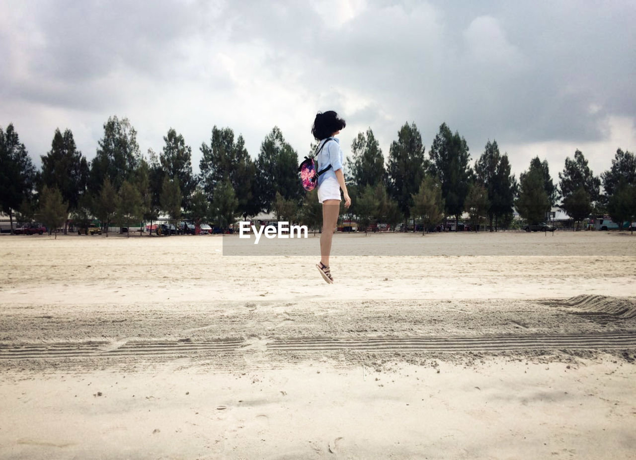 Full length of woman jumping over beach against cloudy sky