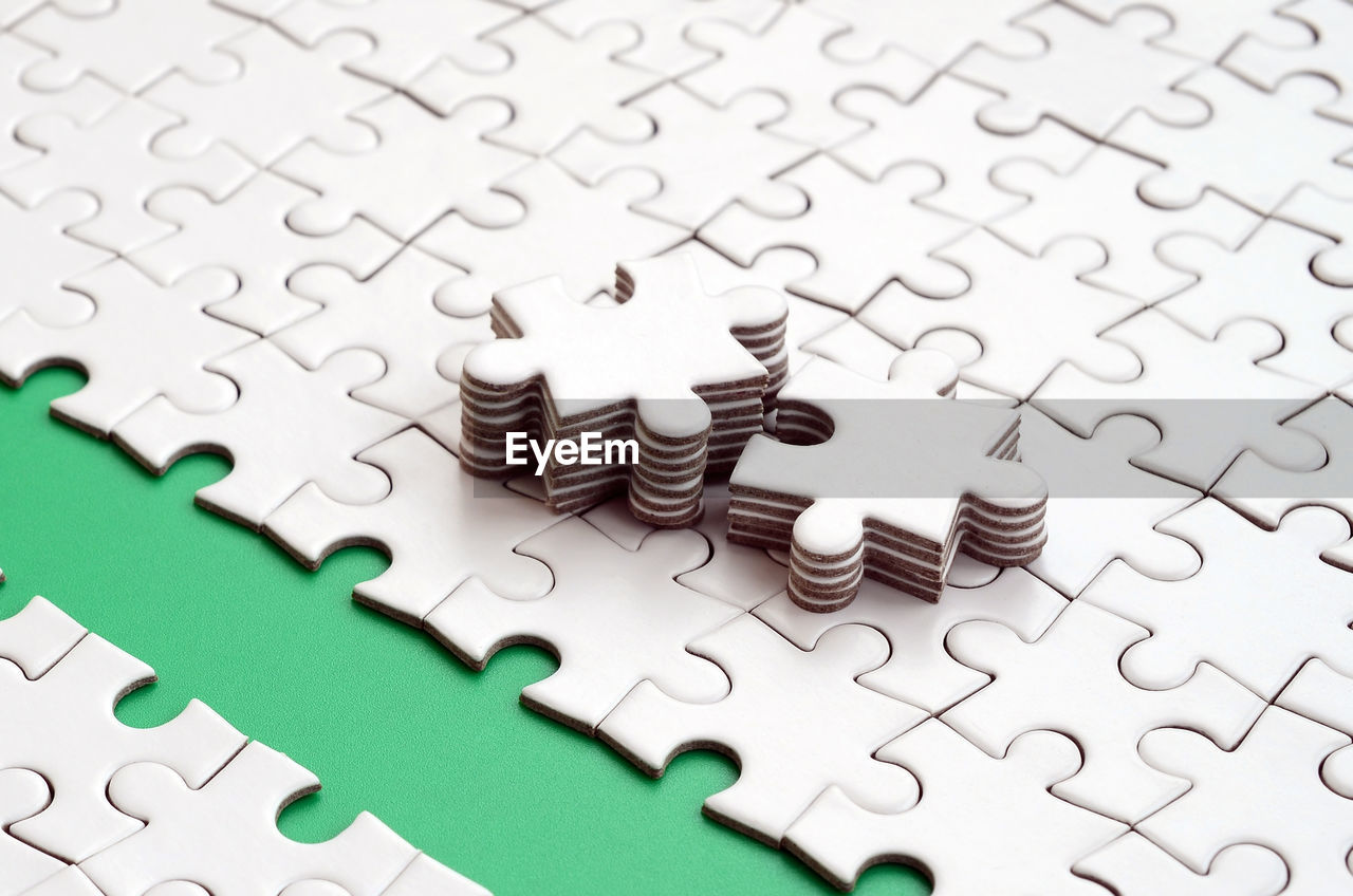 puzzle, jigsaw piece, jigsaw puzzle, connection, solution, pattern, backgrounds, large group of objects, indoors, shape, full frame, white color, no people, leisure activity, strategy, design, green color, leisure games, high angle view, planning, complexity