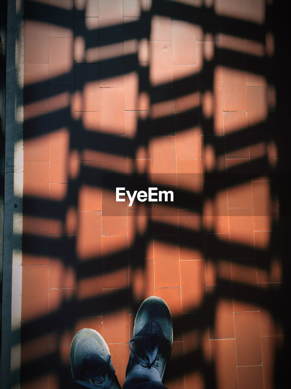 shoe, low section, human body part, one person, real people, body part, human leg, lifestyles, outdoors, standing, leisure activity, shadow, day, personal perspective, unrecognizable person, sunlight, directly above, nature, human foot, flooring, tiled floor, human limb