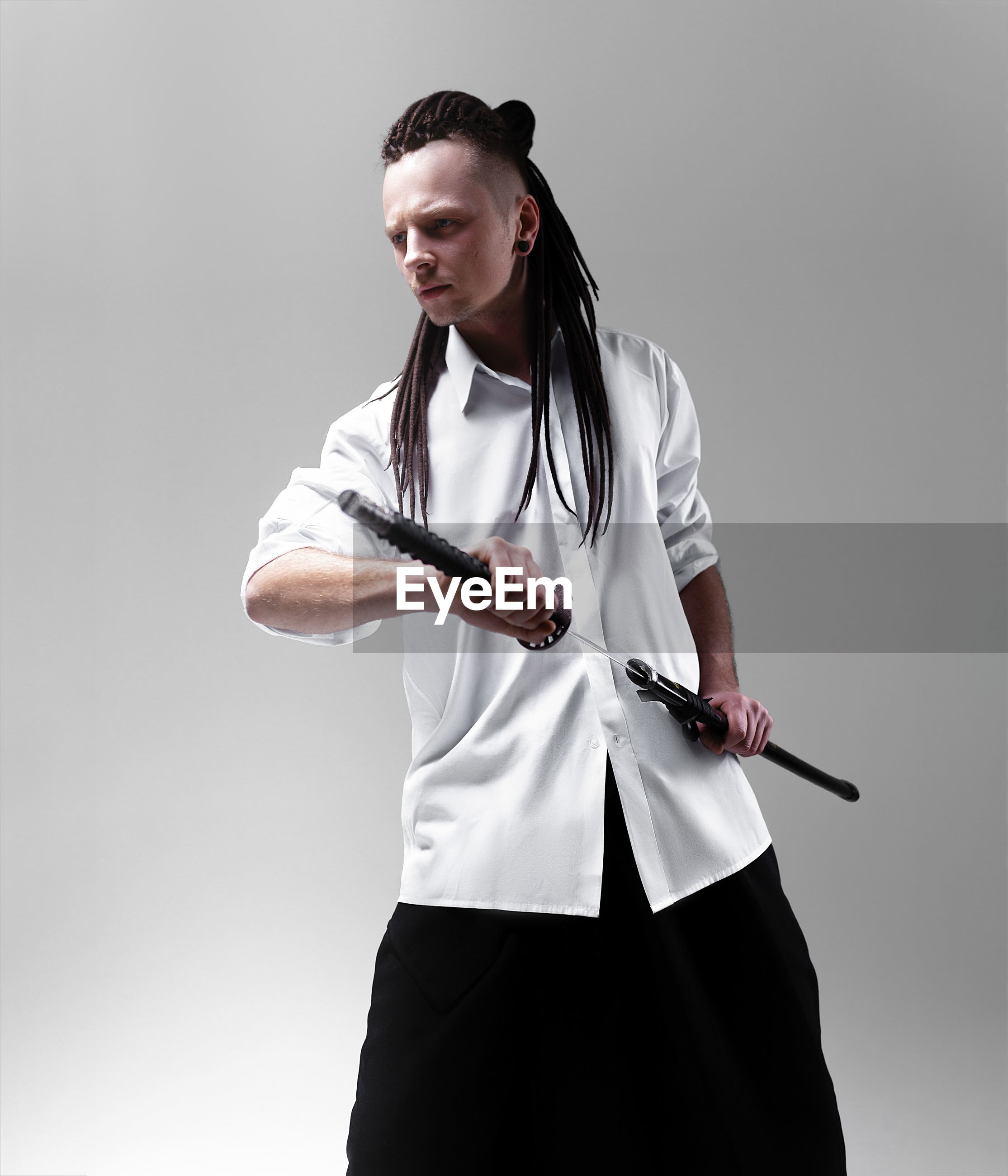 Young man dressed in samurai standing against white background