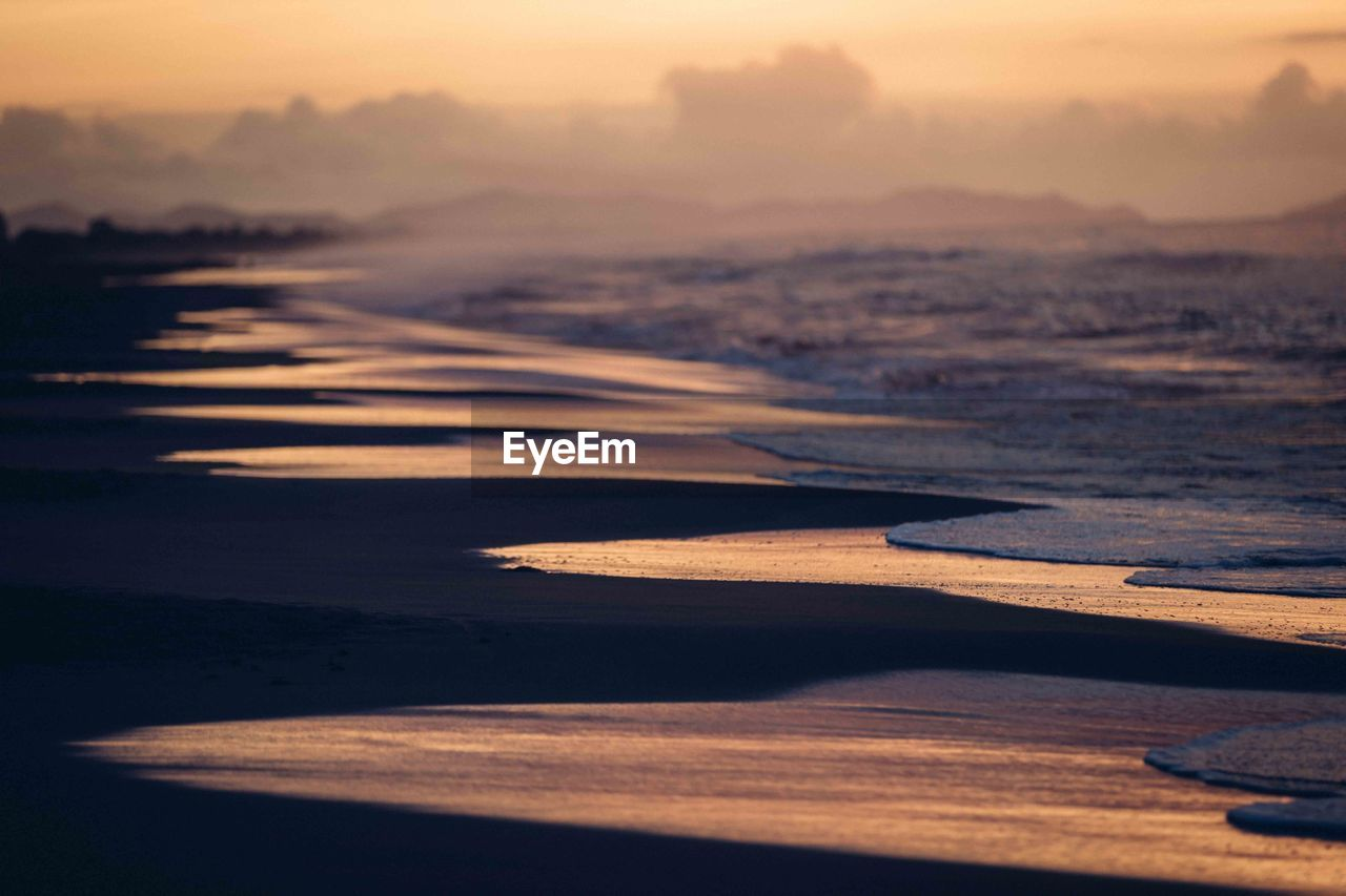 sunset, water, beach, sea, sky, land, nature, tranquility, beauty in nature, tranquil scene, scenics - nature, no people, sunlight, sand, outdoors, idyllic, orange color, wave, selective focus