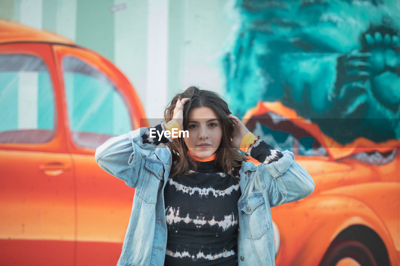 one person, front view, real people, young adult, leisure activity, clothing, lifestyles, waist up, standing, young women, mode of transportation, portrait, jacket, looking at camera, orange color, transportation, focus on foreground, day, warm clothing, beautiful woman, hairstyle, contemplation