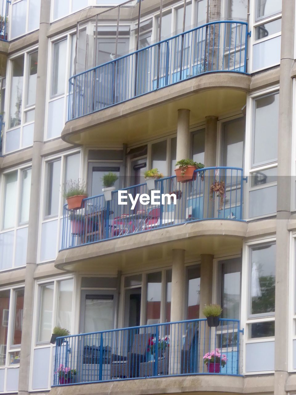 building exterior, architecture, window, balcony, built structure, low angle view, day, outdoors, men, city, people