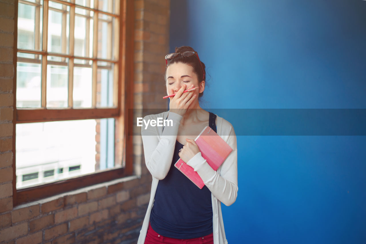 Woman yawning while standing against wall