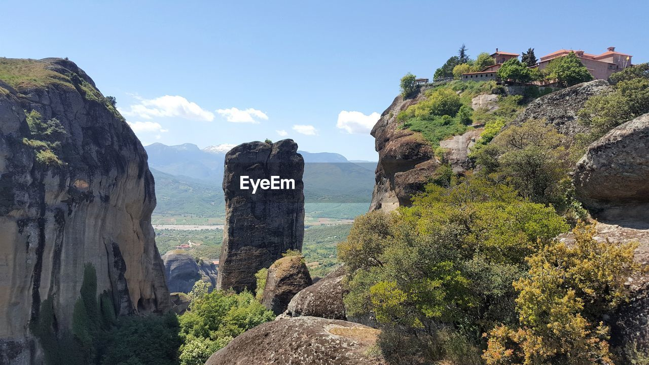 Panoramic view of meteora rocks and plants against sky