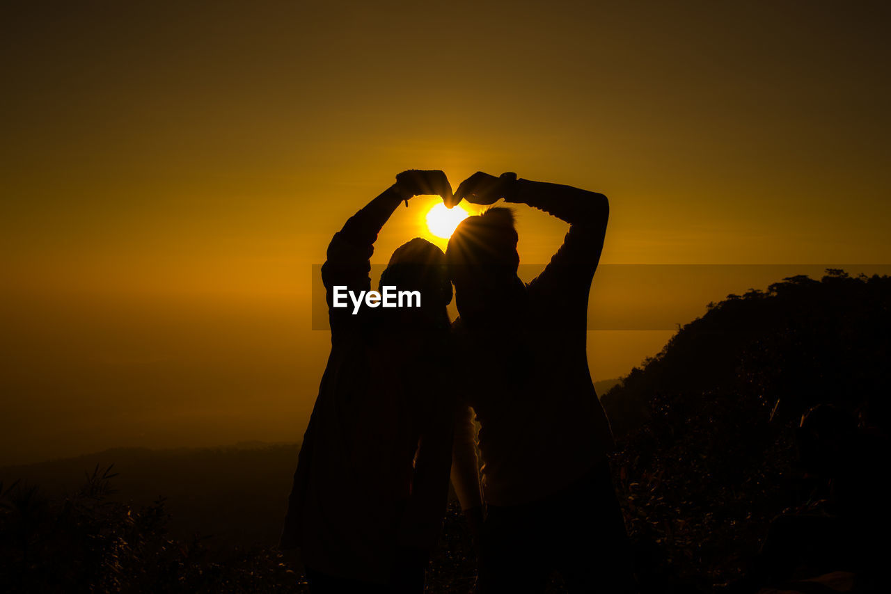 Silhouette of couple making heart shape against sky during sunset