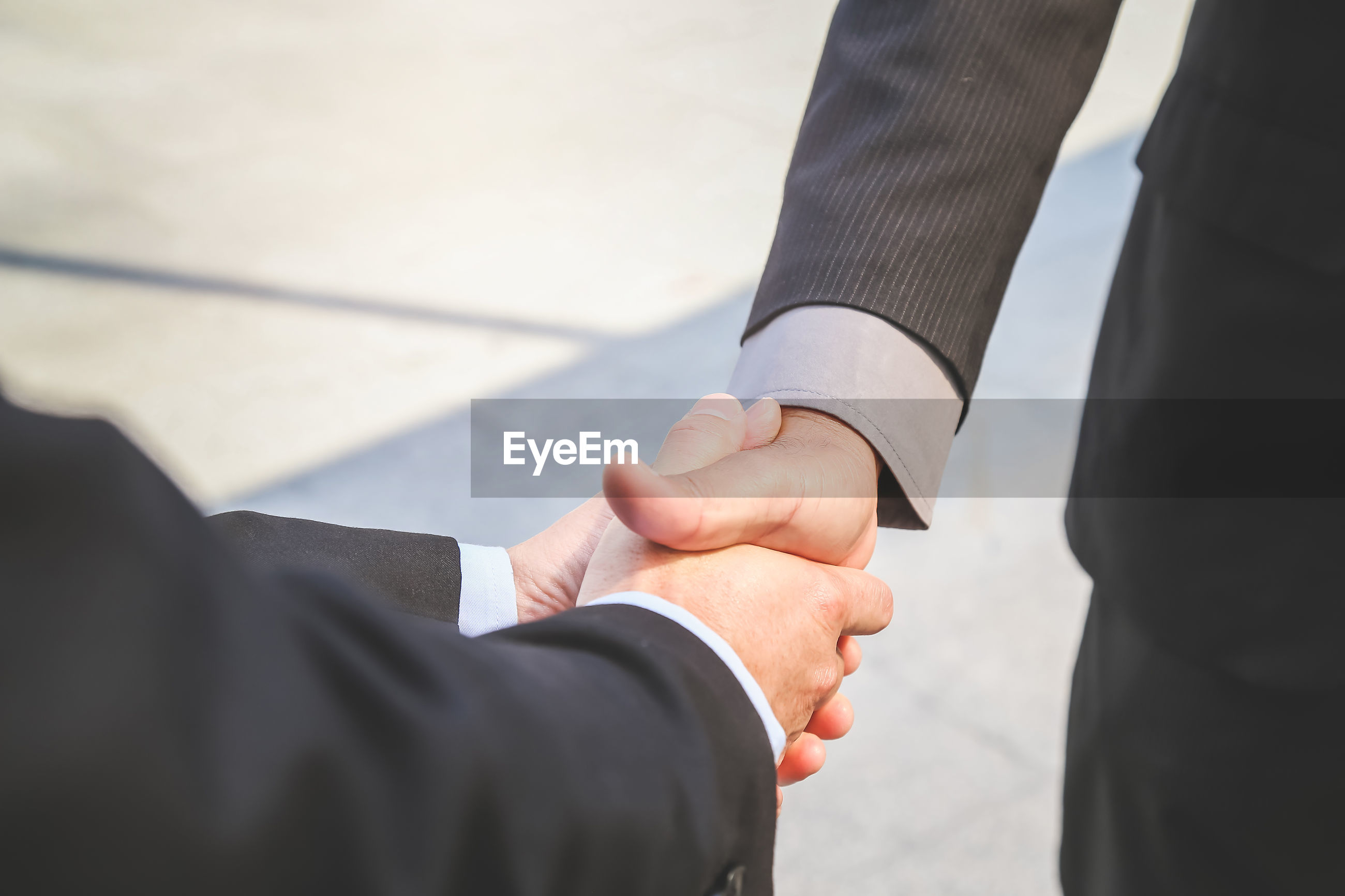 Close-up of business colleagues shaking hands outdoors