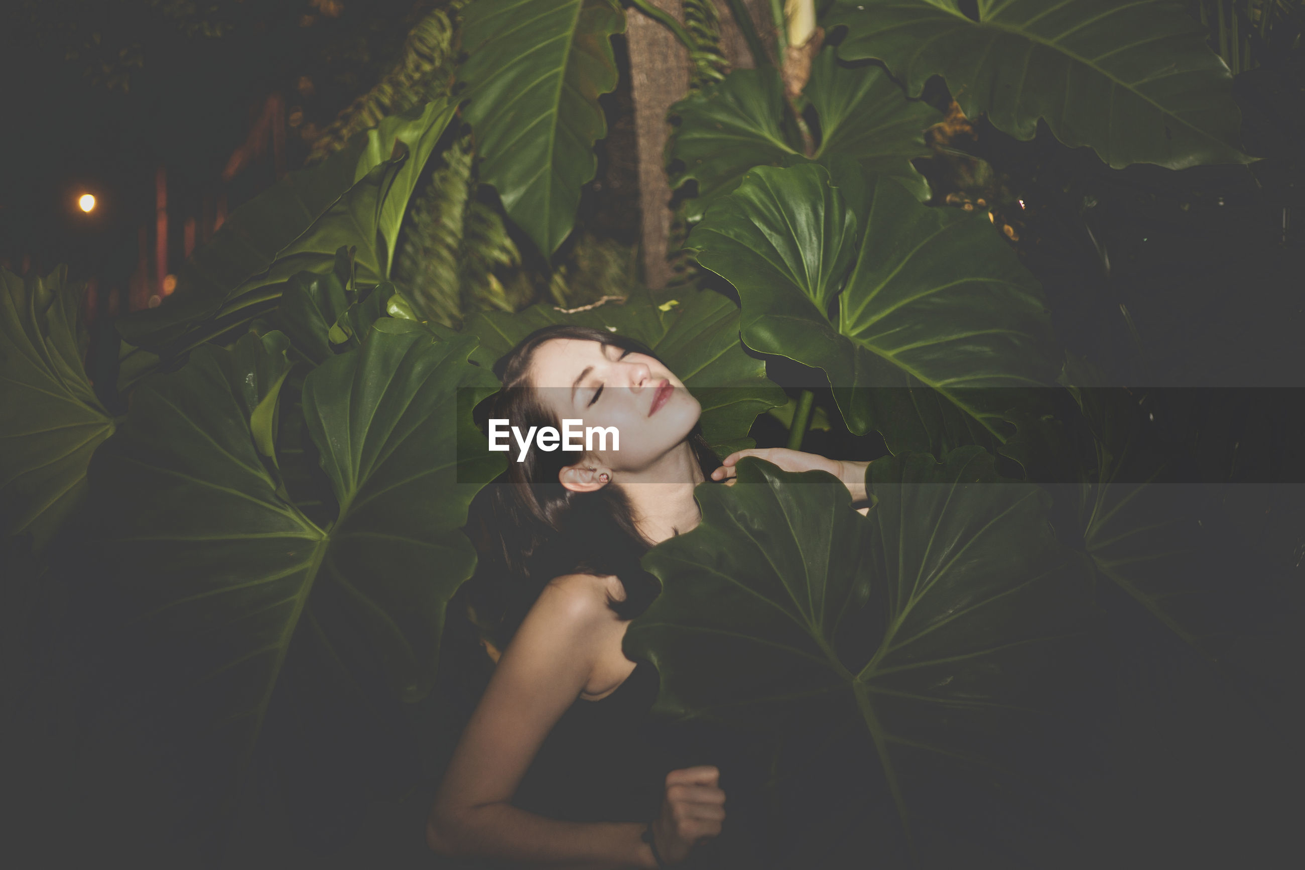 Beautiful young woman with eyes closed standing amidst plants at night