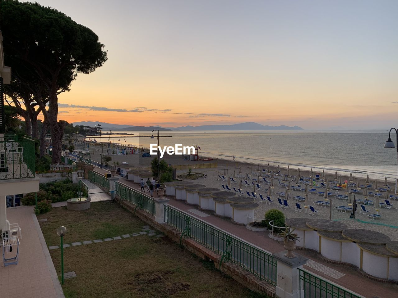 sunset, sky, sea, water, architecture, horizon over water, scenics - nature, nature, beauty in nature, plant, horizon, tree, land, built structure, orange color, beach, tranquility, building exterior, tranquil scene, no people, outdoors