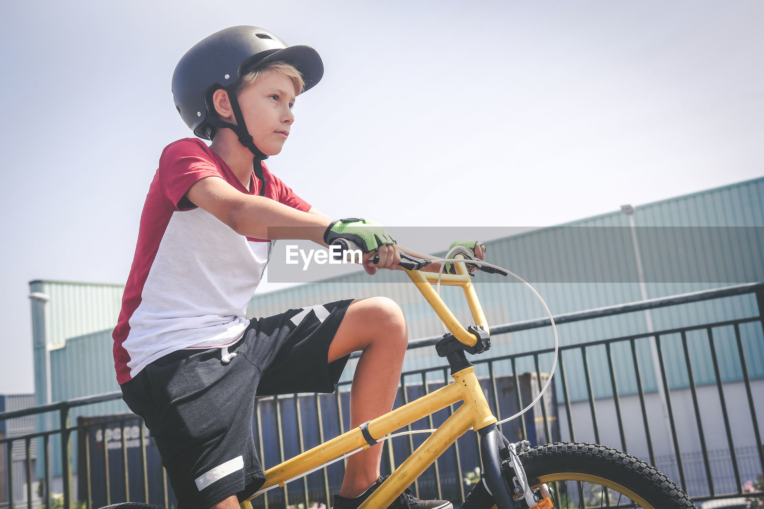 Boy riding bicycle against clear sky