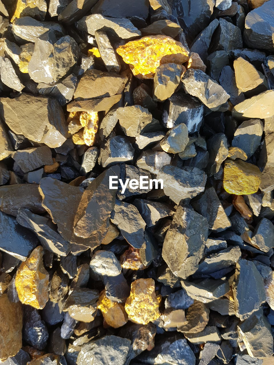 full frame, backgrounds, large group of objects, rock, abundance, no people, solid, day, nature, rock - object, high angle view, textured, stone - object, outdoors, yellow, sunlight, close-up, stack, stone, pattern, pebble