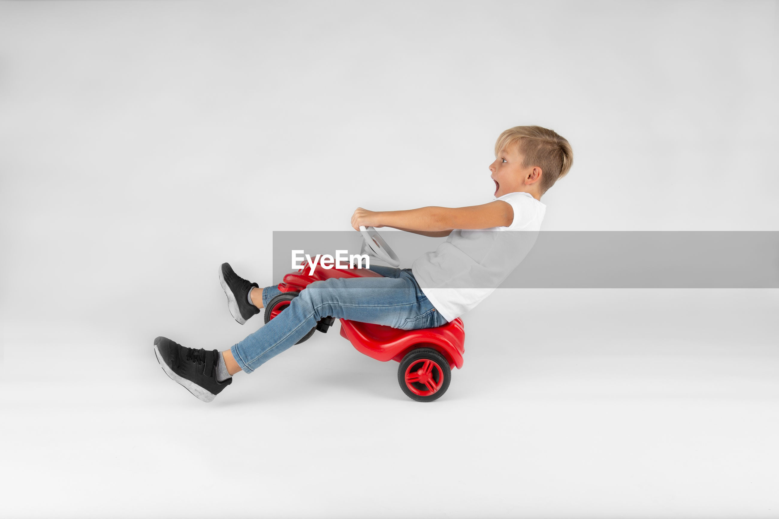 Side view of boy playing with toy car against white background