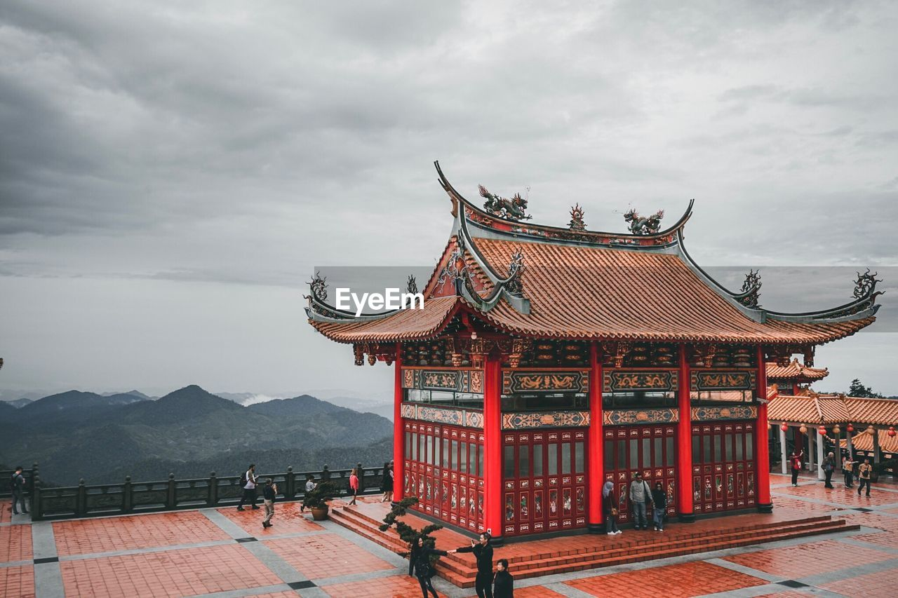 cloud - sky, built structure, sky, architecture, building exterior, religion, place of worship, building, belief, roof, spirituality, nature, day, travel destinations, mountain, travel, incidental people, outdoors, shrine