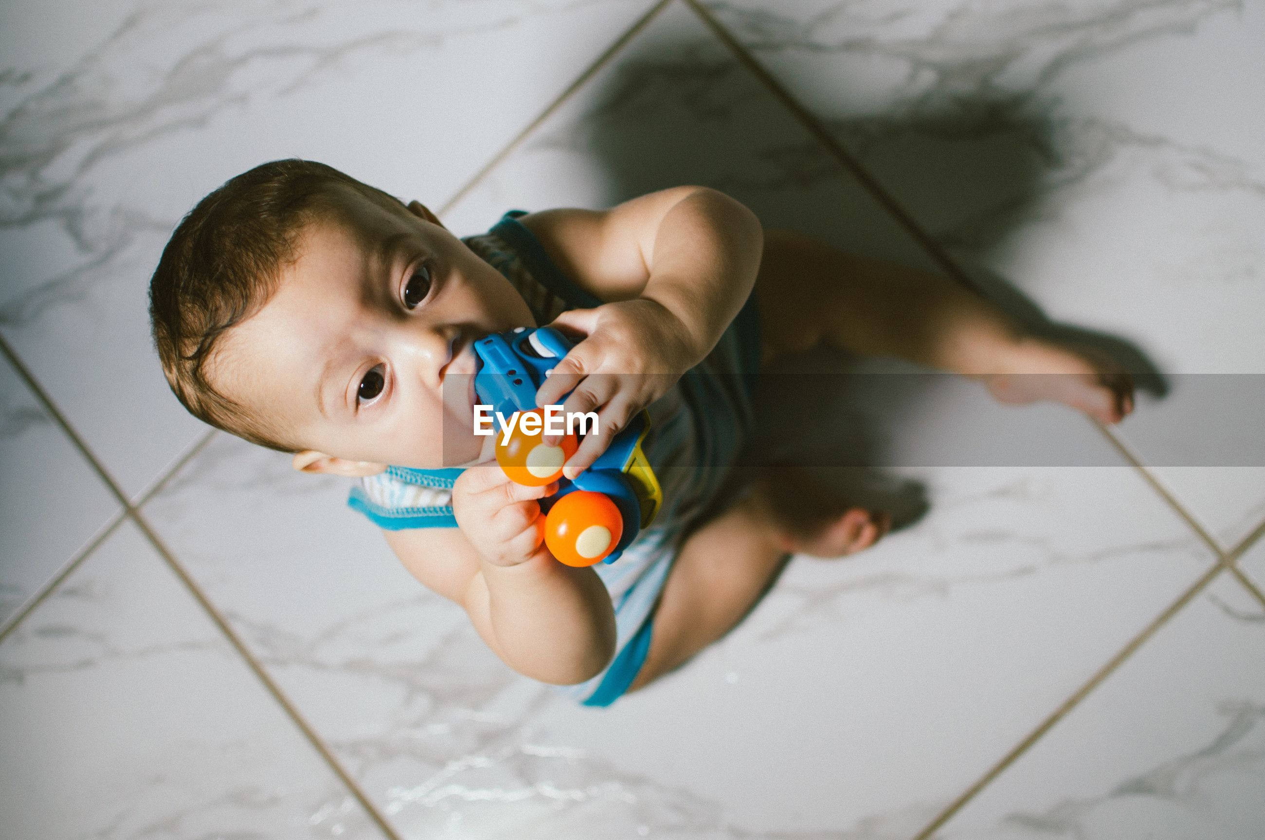 High angle view of baby boy holding toy on floor at home