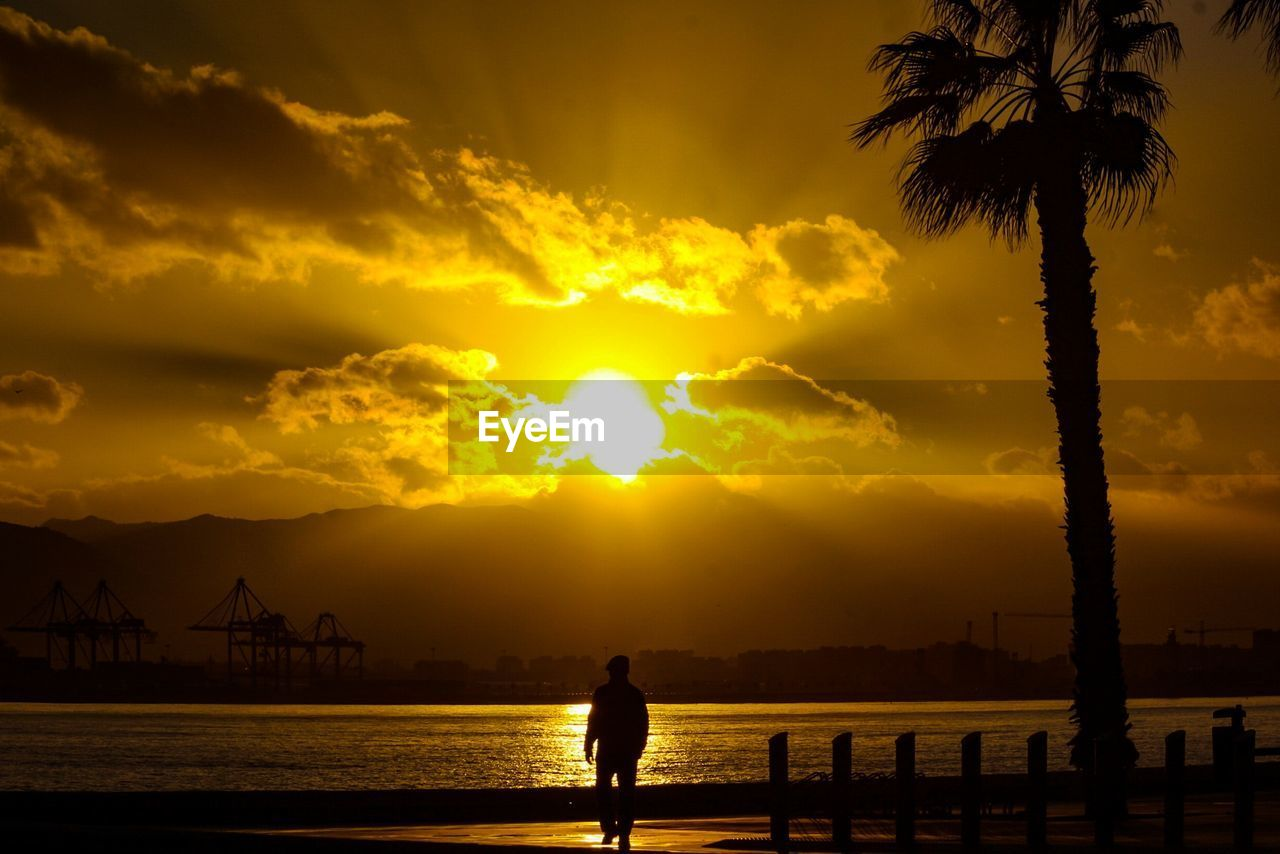 sky, sunset, silhouette, water, beauty in nature, orange color, cloud - sky, sea, nature, scenics - nature, tree, lifestyles, real people, one person, architecture, leisure activity, tranquil scene, palm tree, tropical climate, outdoors