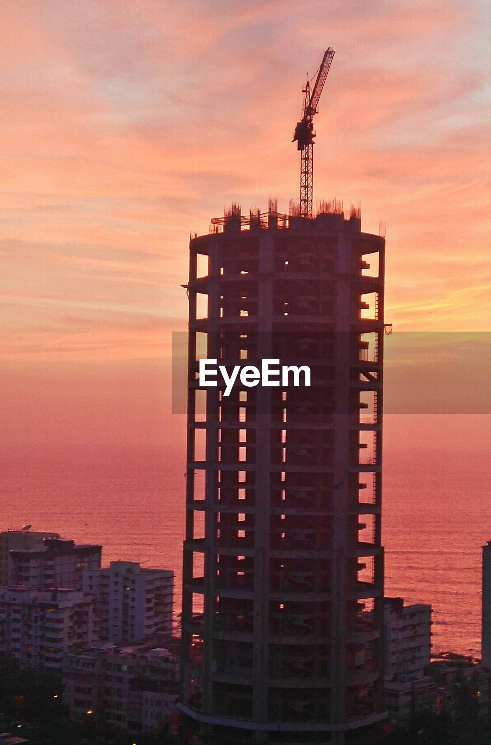 sunset, architecture, building exterior, built structure, sky, orange color, tower, tall - high, city, communication, cloud - sky, communications tower, silhouette, skyscraper, travel destinations, development, crane - construction machinery, outdoors, no people, modern