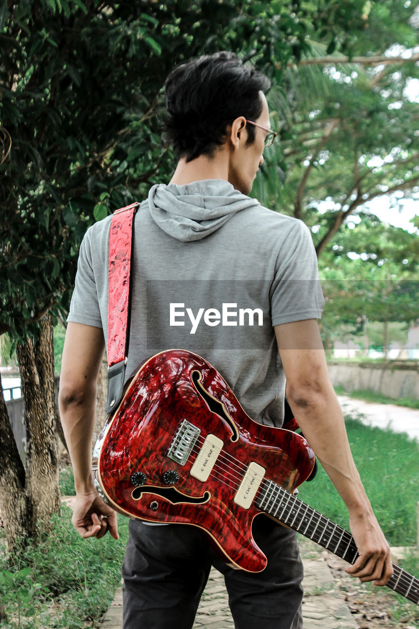FULL LENGTH REAR VIEW OF A MAN HOLDING GUITAR