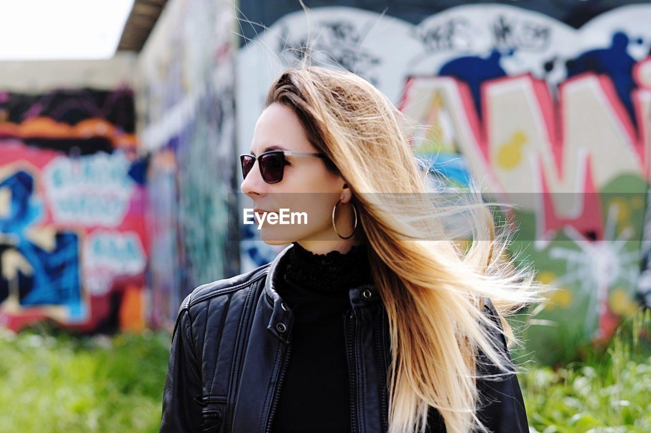 Beautiful Young Woman Wearing Sunglasses Against Graffiti Wall