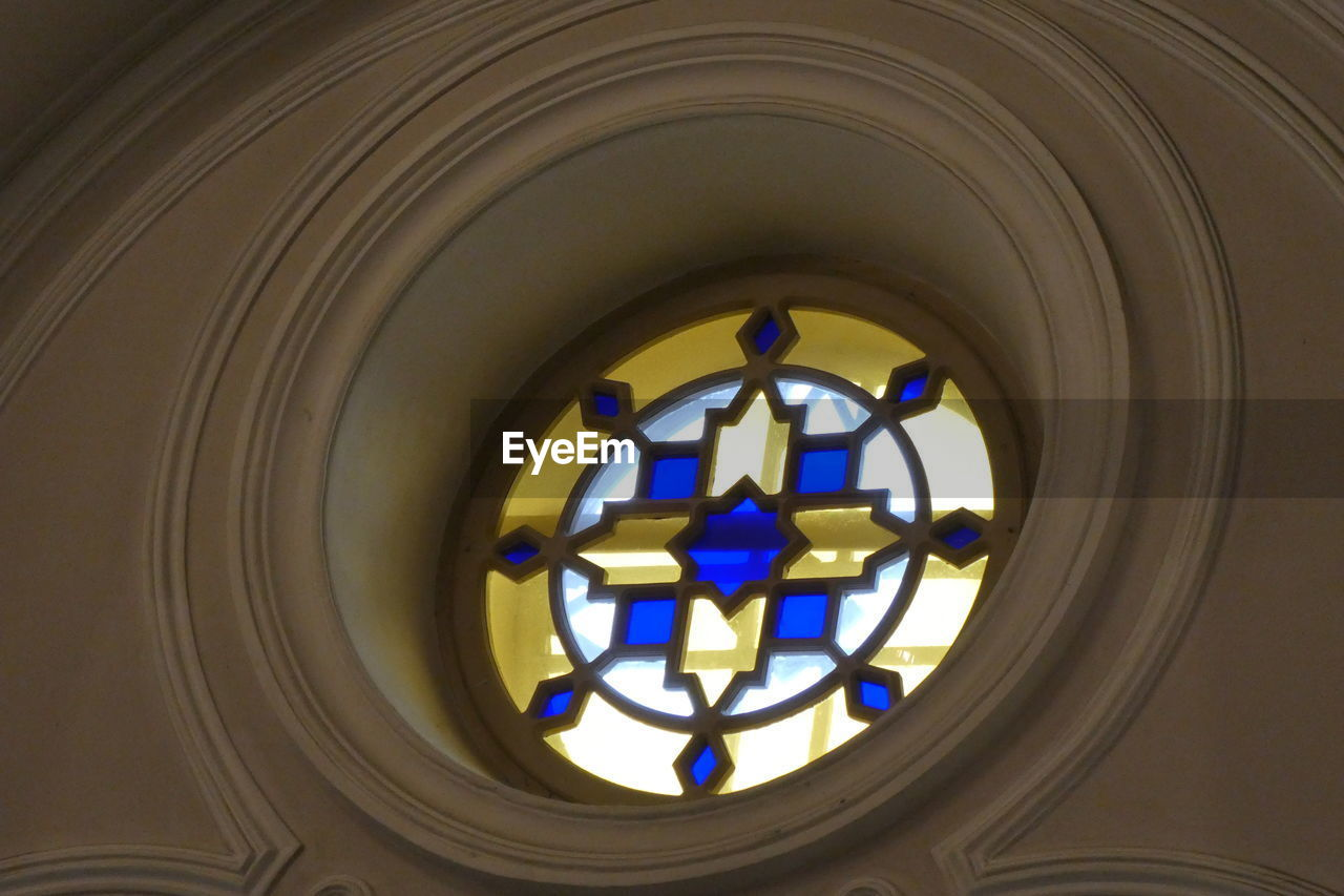indoors, geometric shape, spirituality, architecture, circle, religion, belief, no people, place of worship, stained glass, shape, built structure, window, low angle view, glass - material, glass, pattern, design, ceiling, directly below