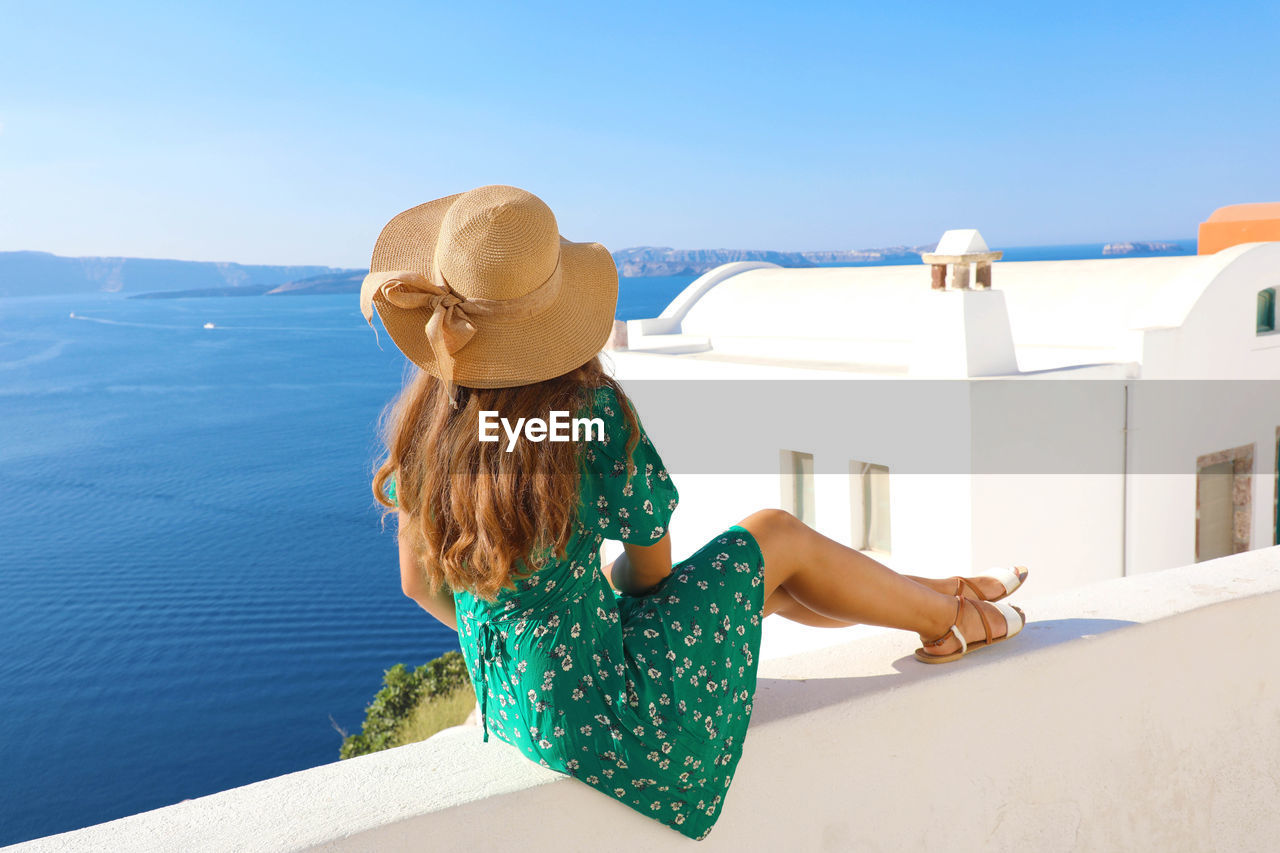 rear view, real people, leisure activity, one person, lifestyles, sky, nature, sea, sunlight, day, clothing, water, architecture, women, built structure, hat, beauty in nature, three quarter length, hair, hairstyle, outdoors, looking at view