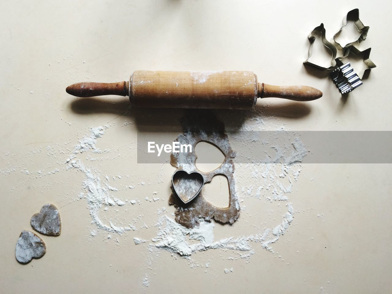High angle view of rolling pin with cookie cutters on table