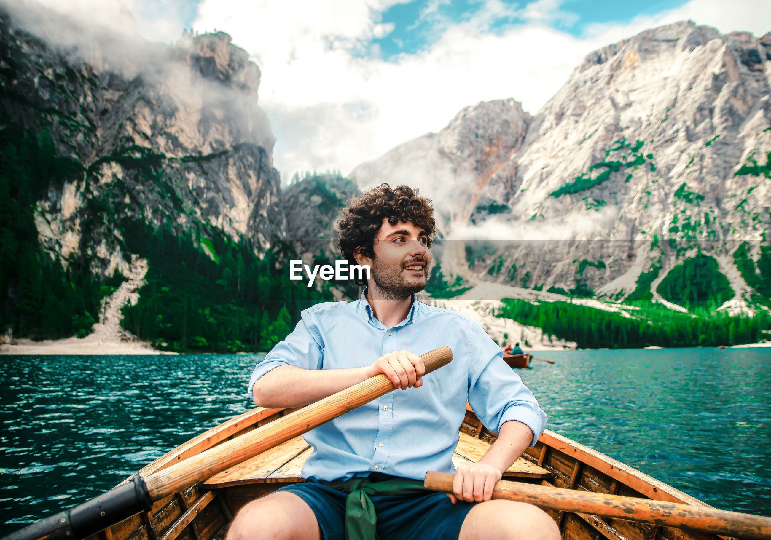 MAN SITTING IN BOAT AGAINST MOUNTAINS