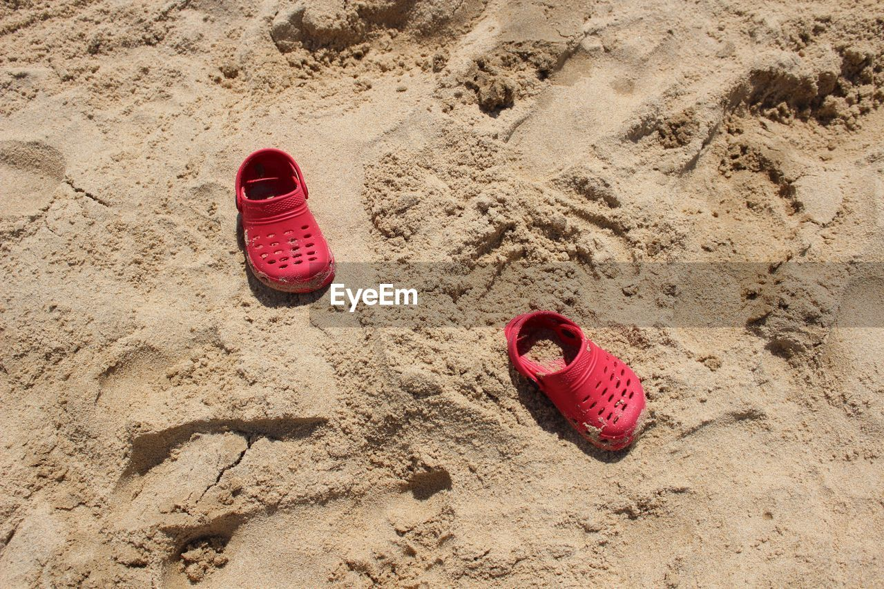 High angle view of child red shoes on sand