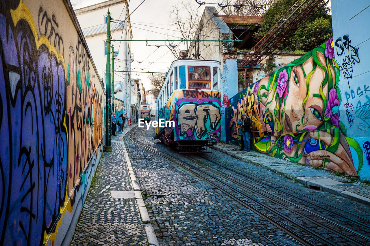 graffiti, rail transportation, track, transportation, railroad track, creativity, multi colored, mode of transportation, day, art and craft, public transportation, street art, architecture, wall - building feature, built structure, outdoors, no people, building exterior, train, train - vehicle, social issues